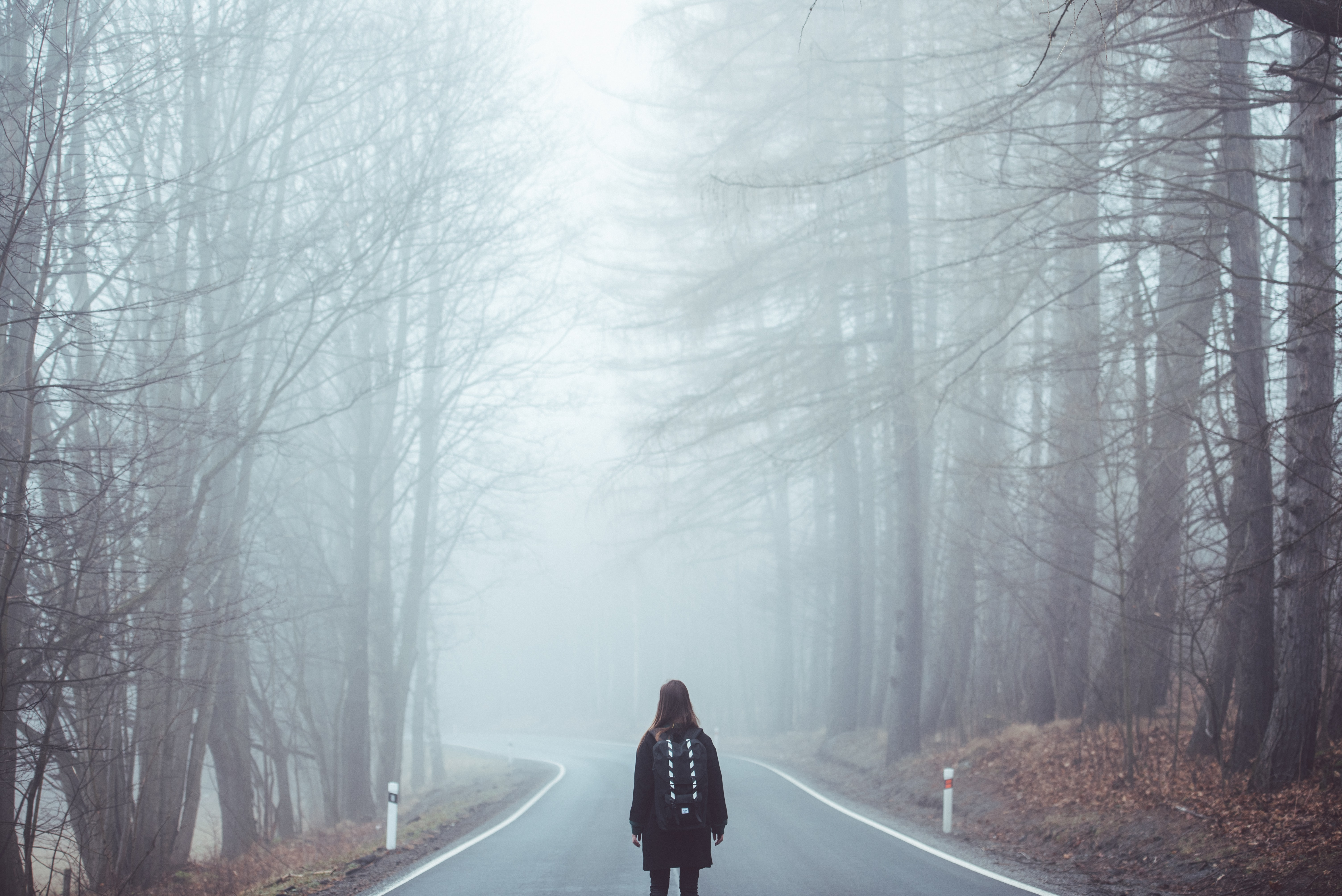 A woman standing in the middle of the road surrounded by mist in Šumava National Park