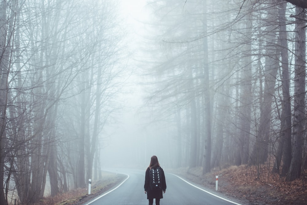 A woman standing in the middle of the road surrounded by mist in Å umava National Park