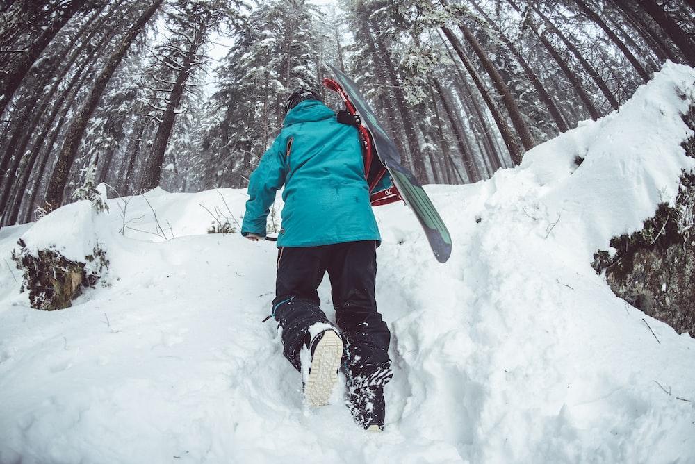 man climbing snow near trees