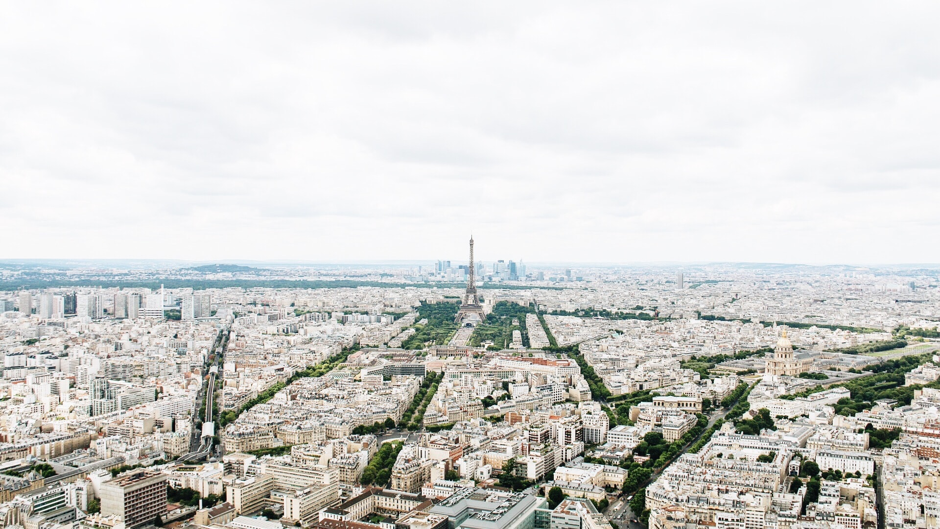 Urban cityscape of Paris with the historic Eiffel Tower at the center.