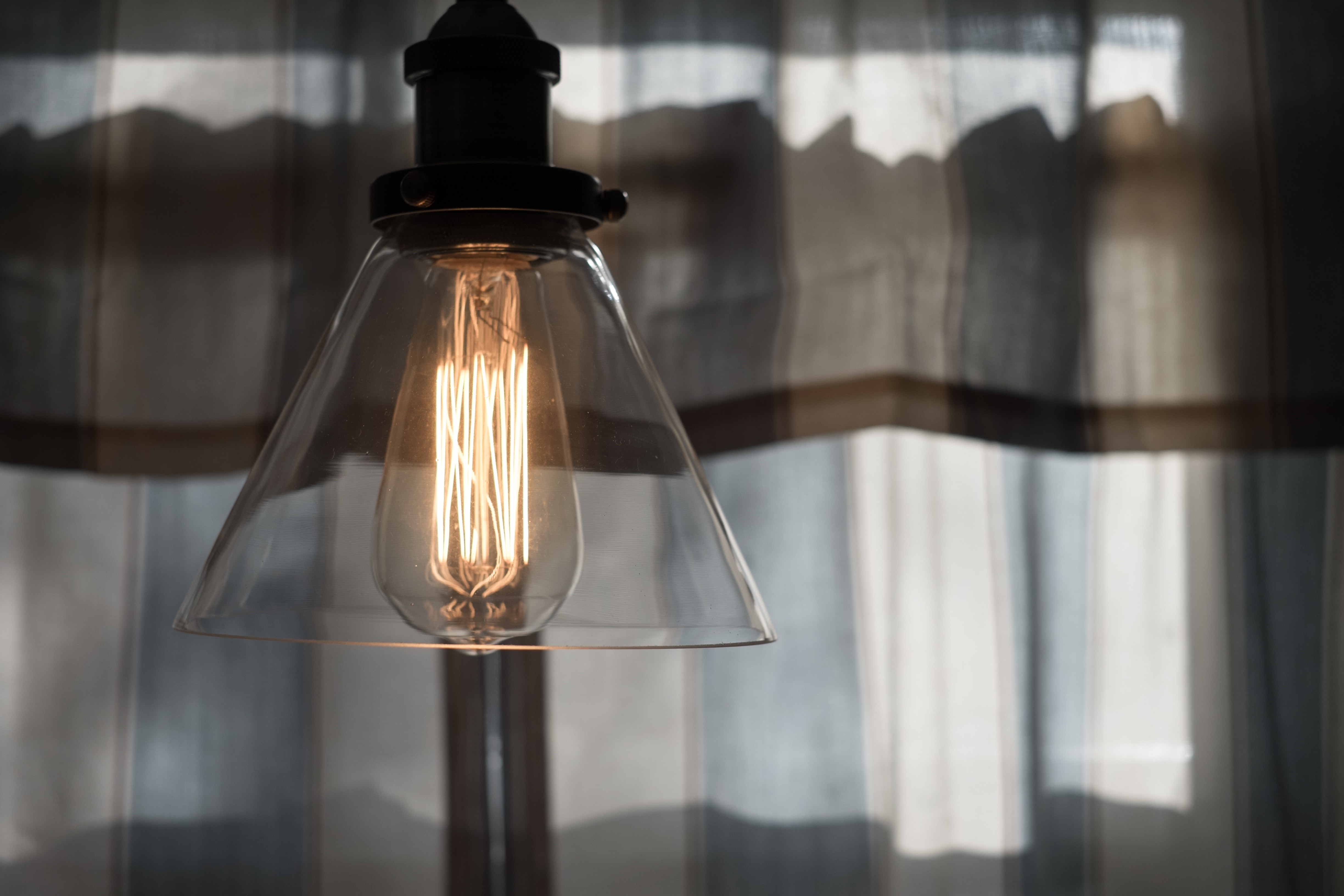 Hanging light in a clear lampshade with light tan curtains in the background