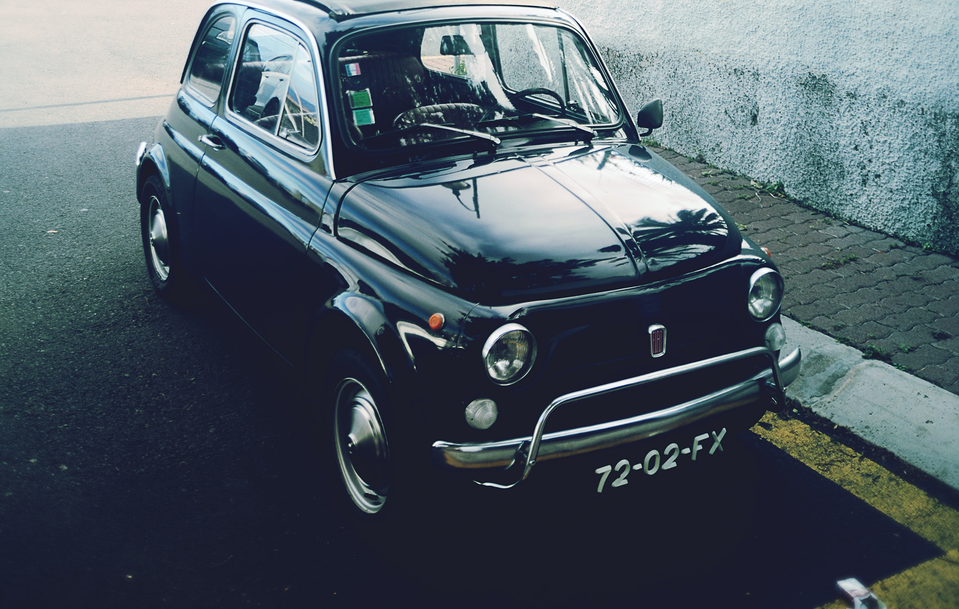 Small vintage Fiat parked on street.