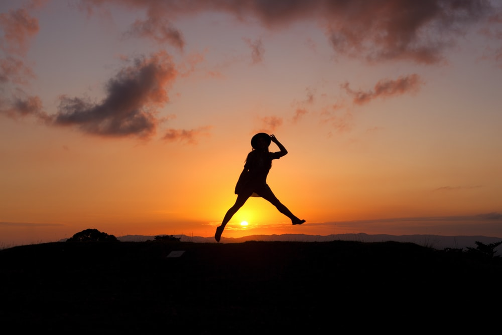 silhouette of human jumping during sunset