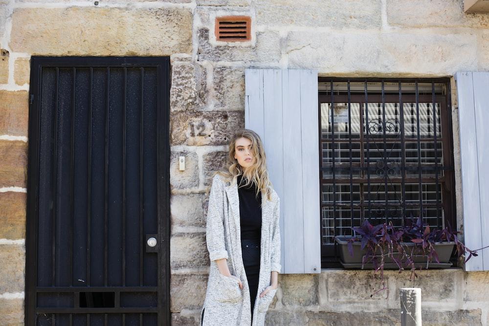 woman wearing gray robe standing near closed storm door