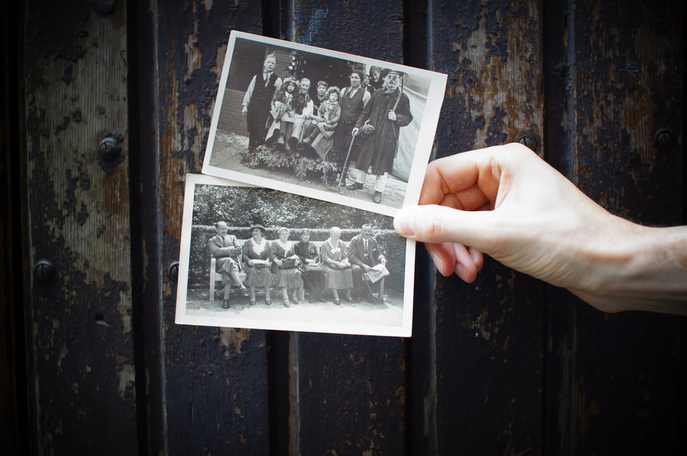 person holding vintage photos