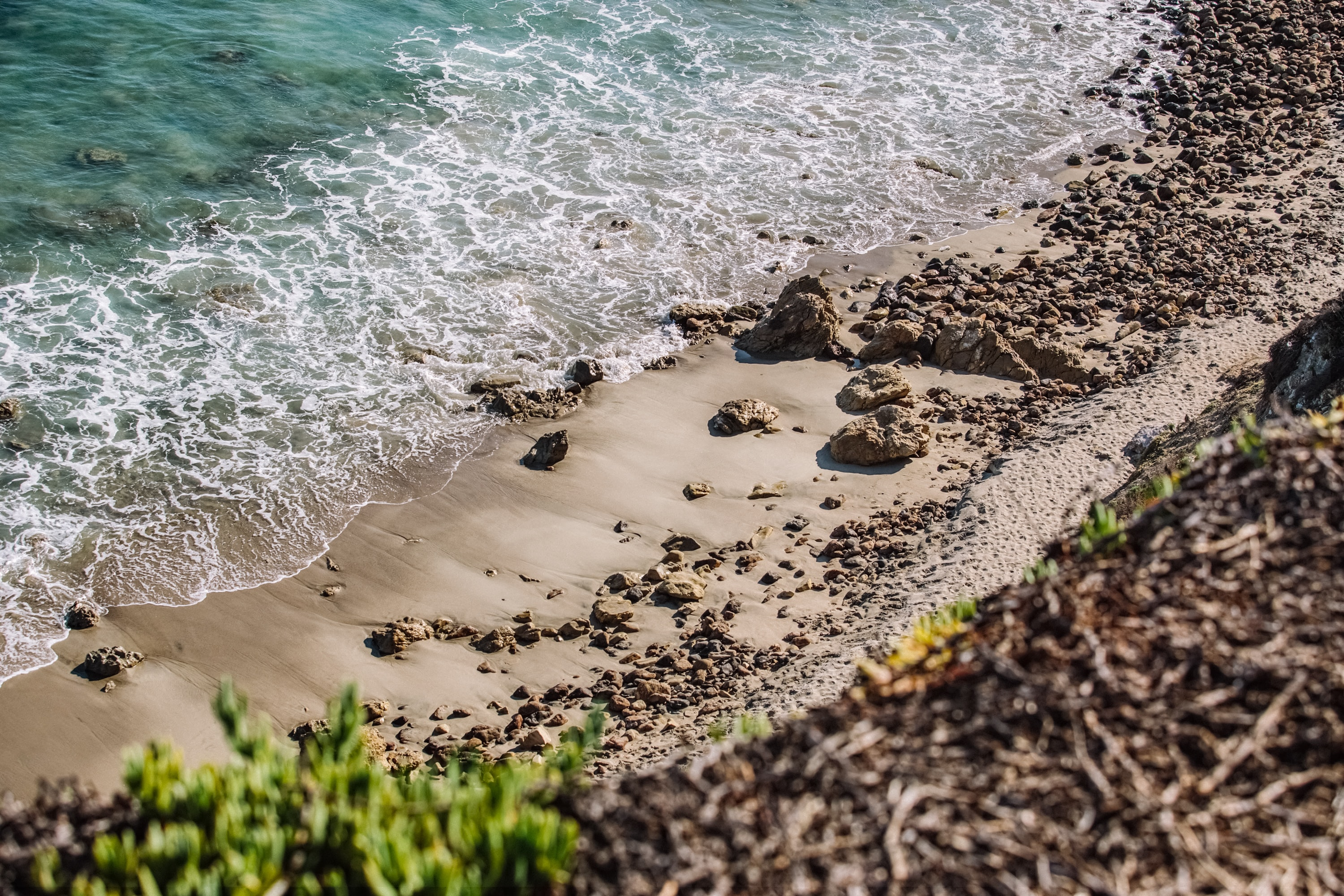 Ocean washing on the sandy and rocky coastline viewed from the hill above at Point Dume State Beach