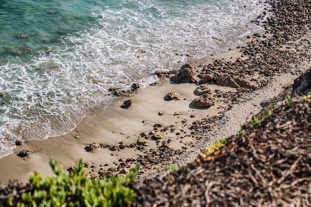 aerial photography of waves splashing on seashore