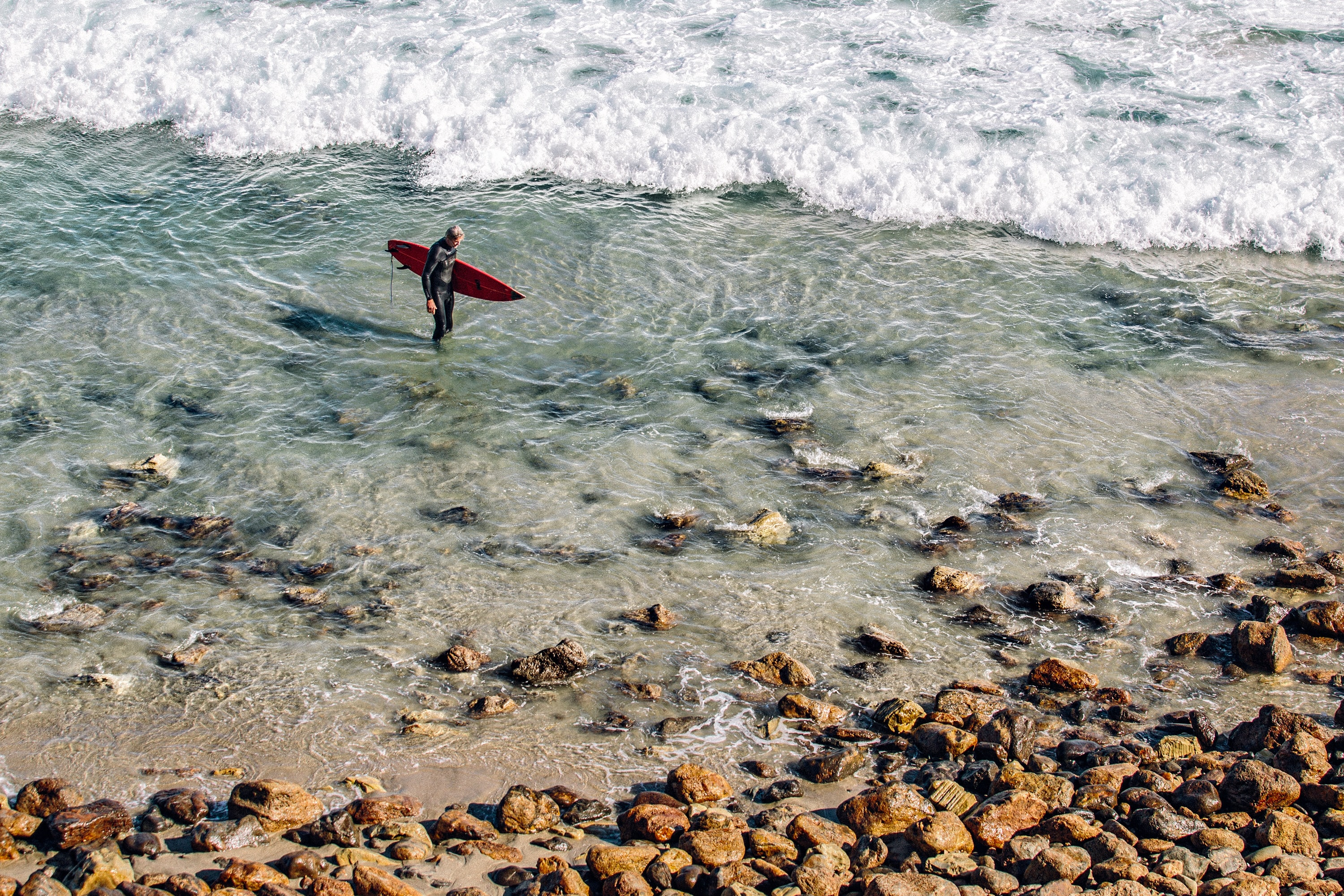 Surfer with a surfboard standing in the shallow ocean water at Point Dume State Beach