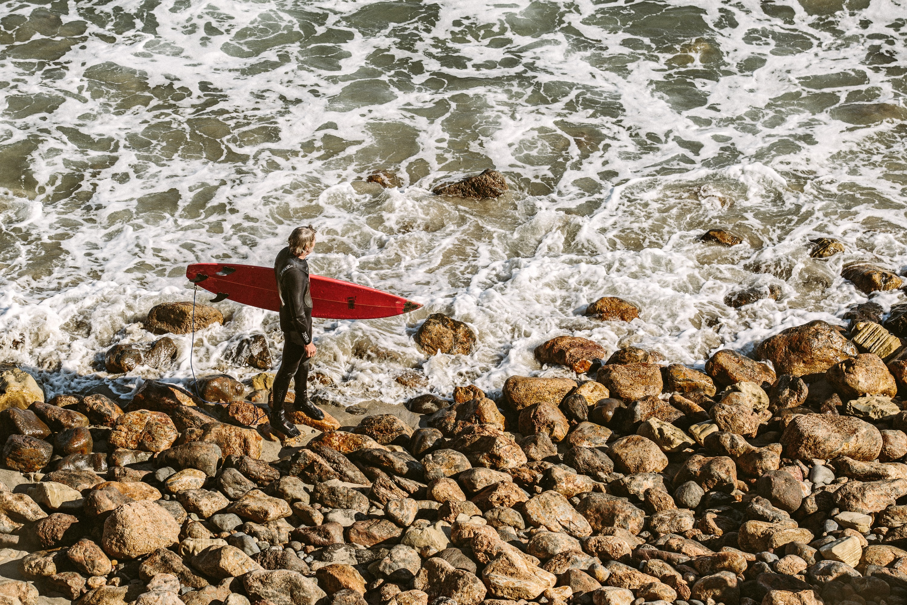 person holding surfboard near seashore during daytime