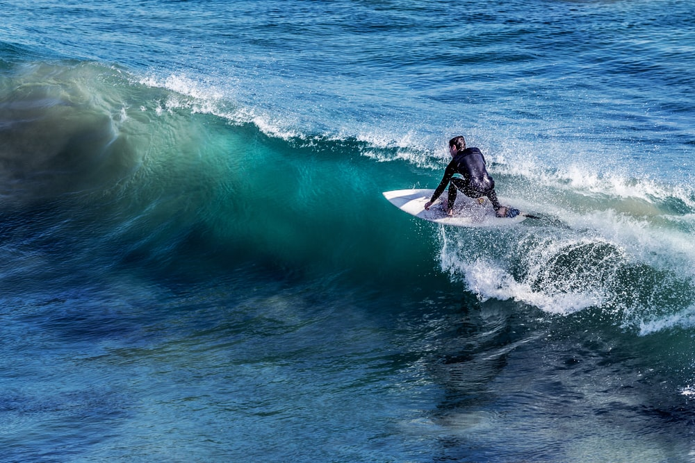 person on white surfboard surrounded by blue ocean water during daytime