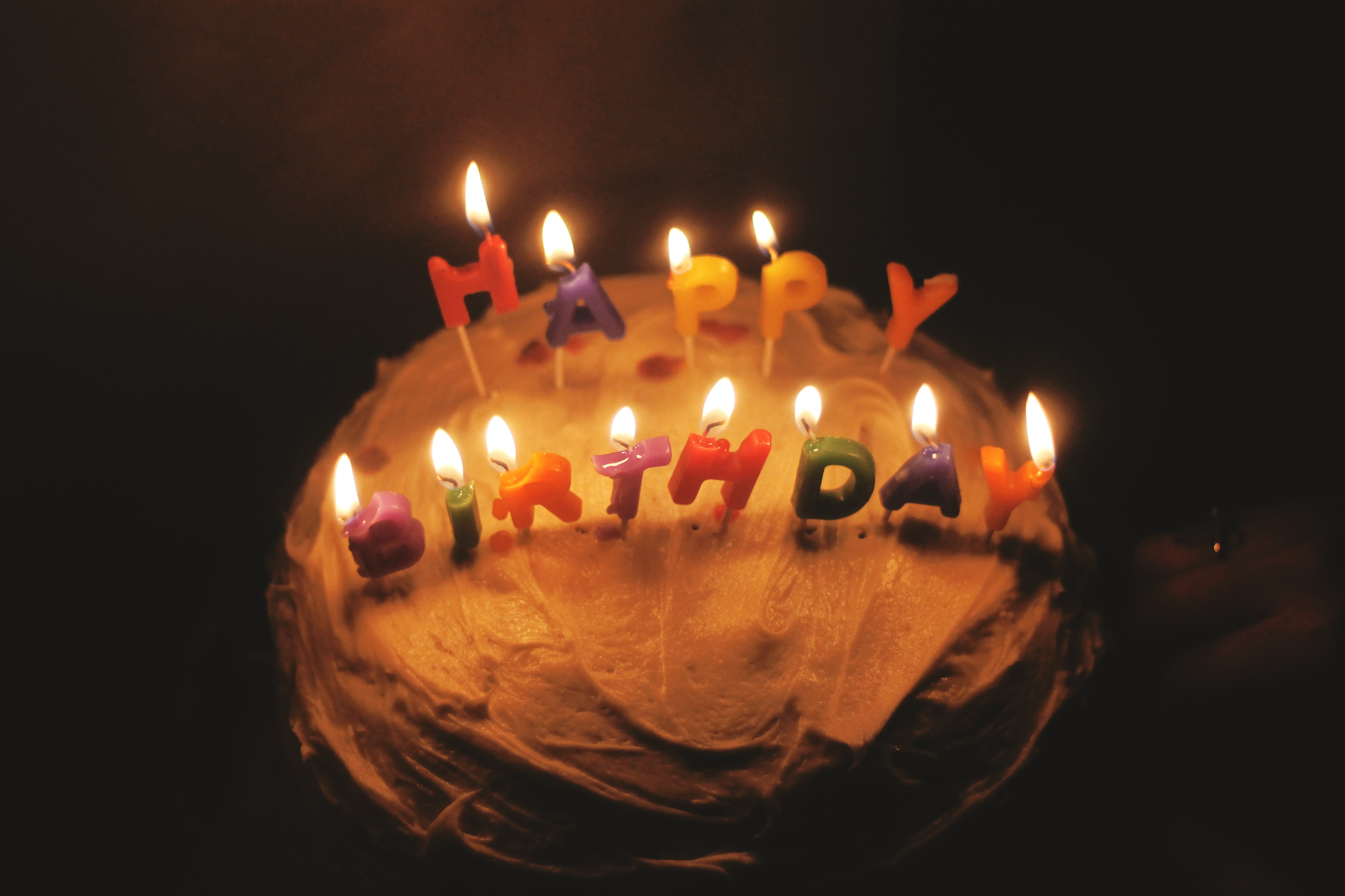 A birthday cake with frosting and happy birthday candles burning in a dark room