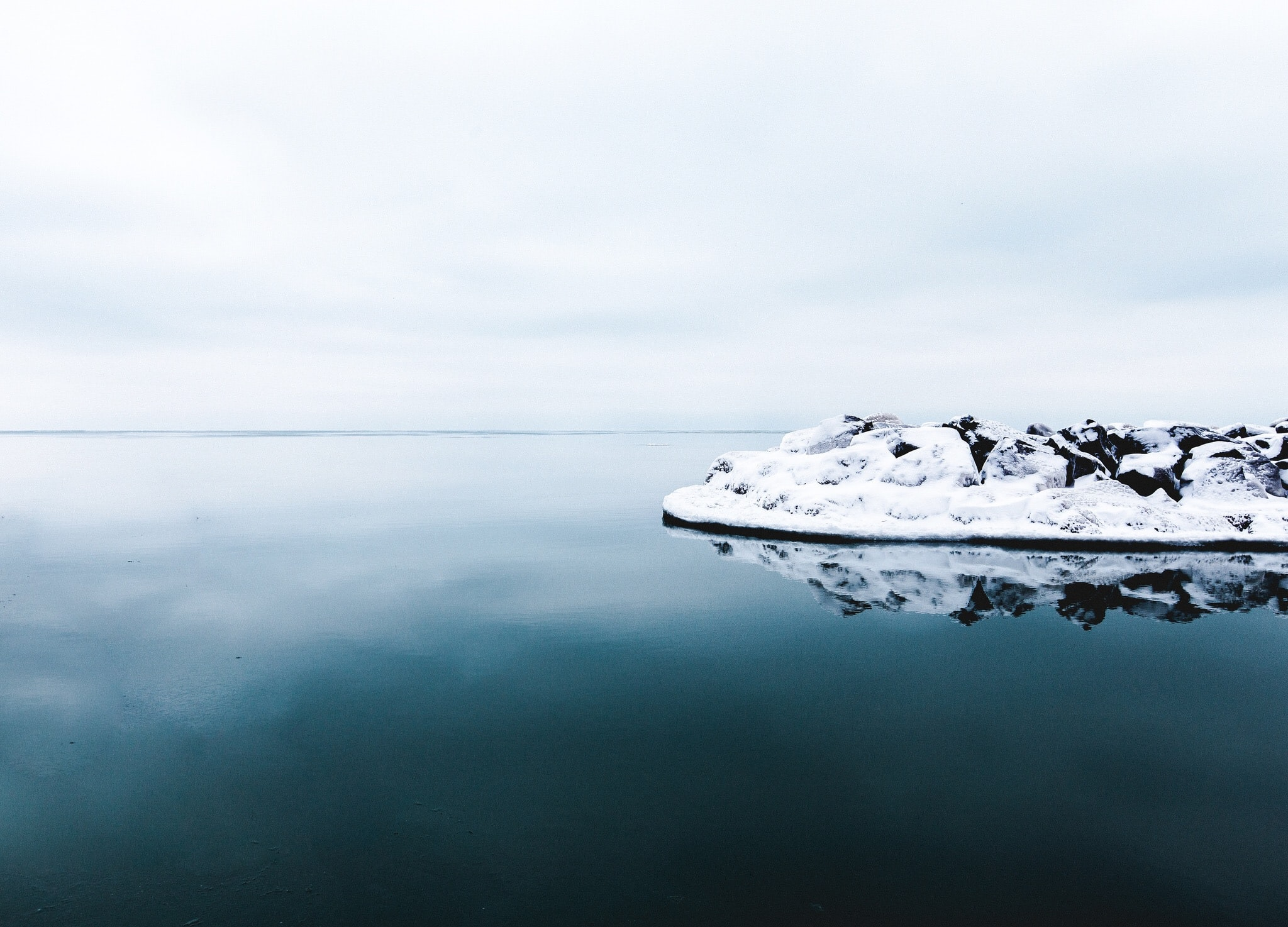 The reflection of a snow covered rock in dark blue water