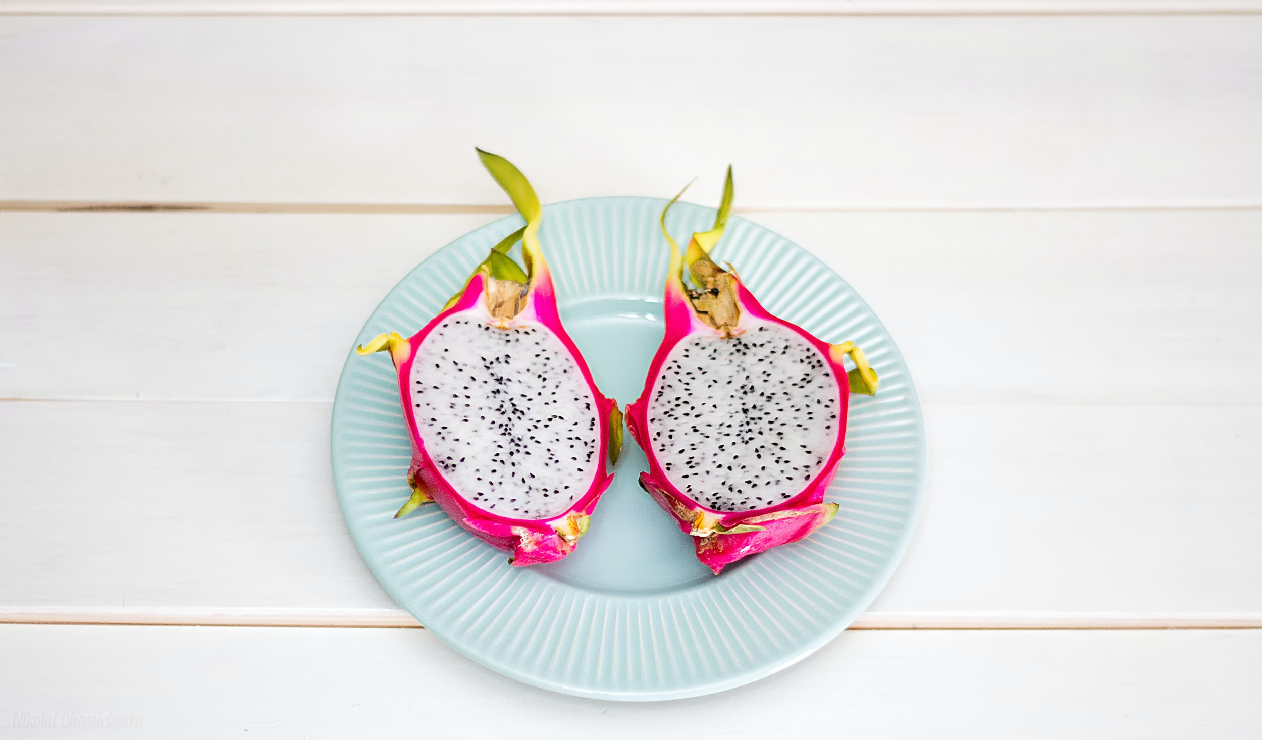 2-sliced dragon fruit in ceramic plate placed on wood plank