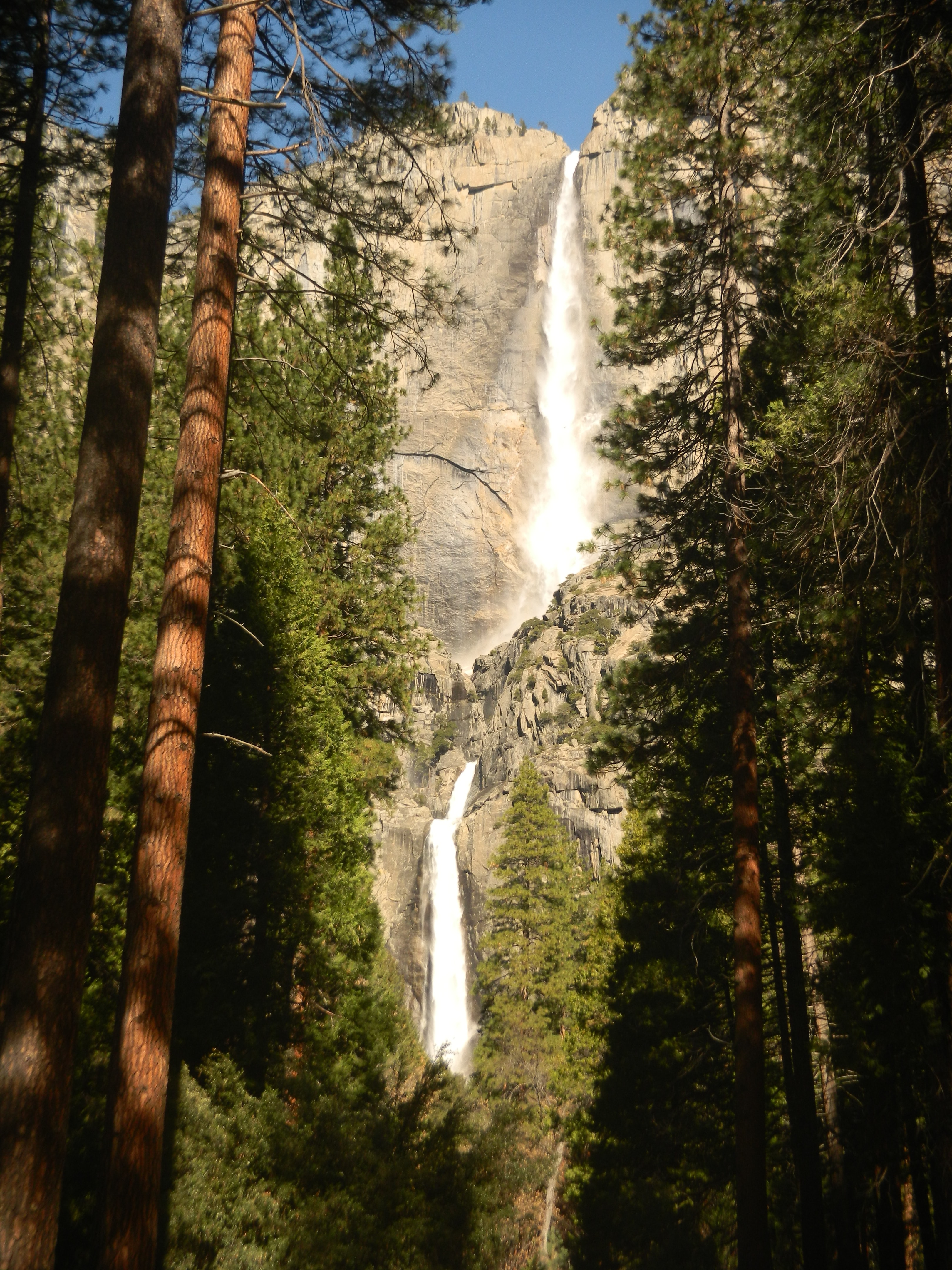 A look up at a waterfall pouring down a rocky mountain in Yosemite National Park