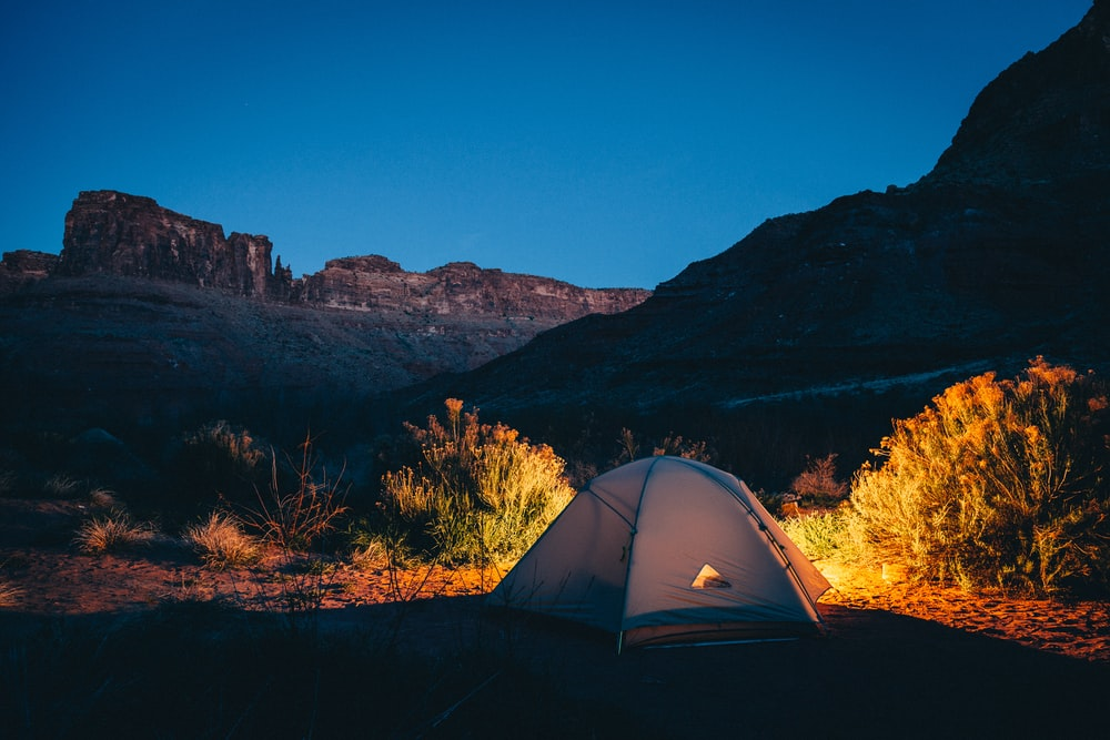 white camping tent beside mountain