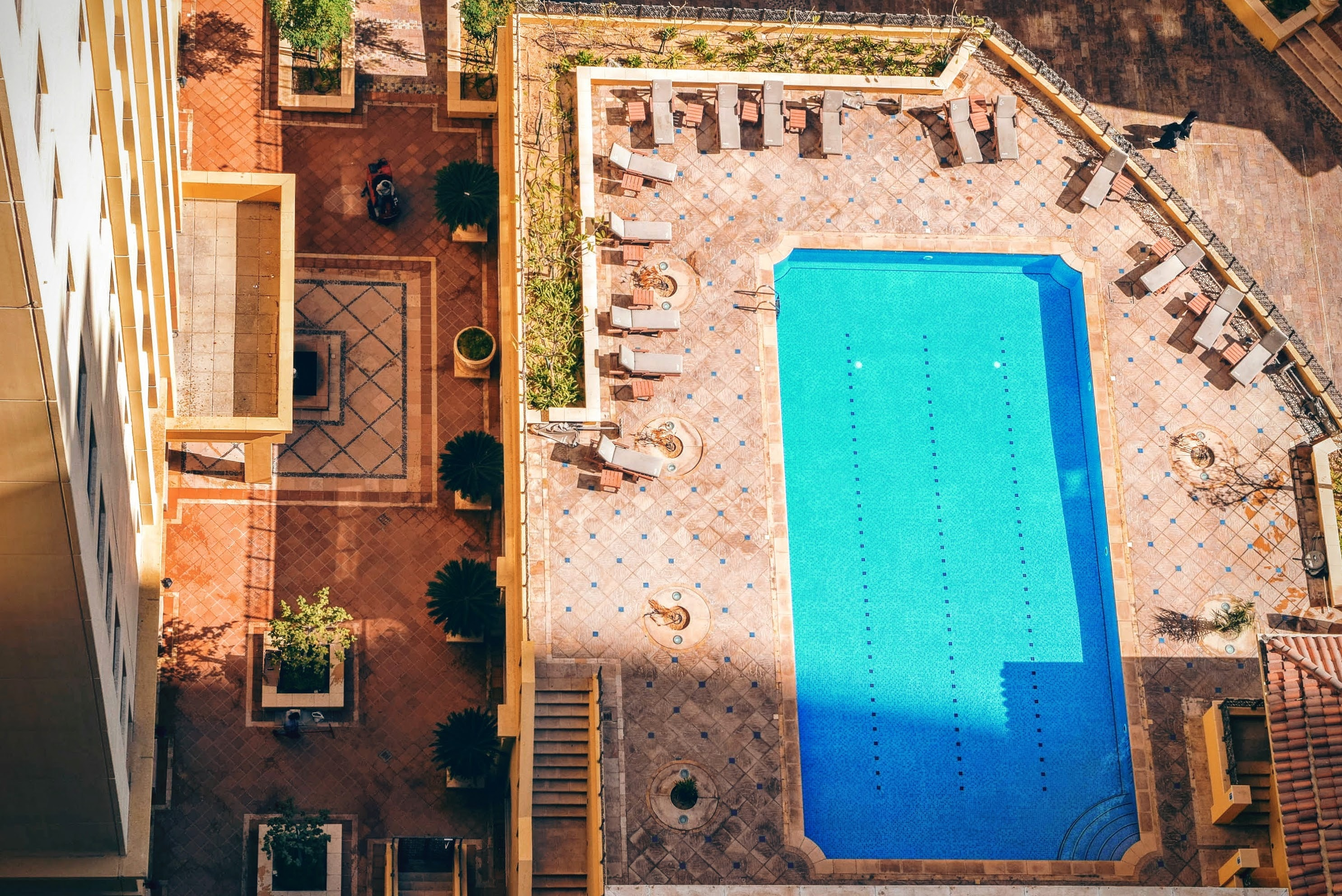 Drone view of pool near building surrounded by lounger deck chairs
