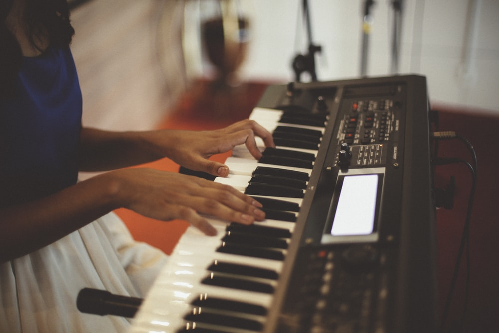 person playing a black electronic keyboard