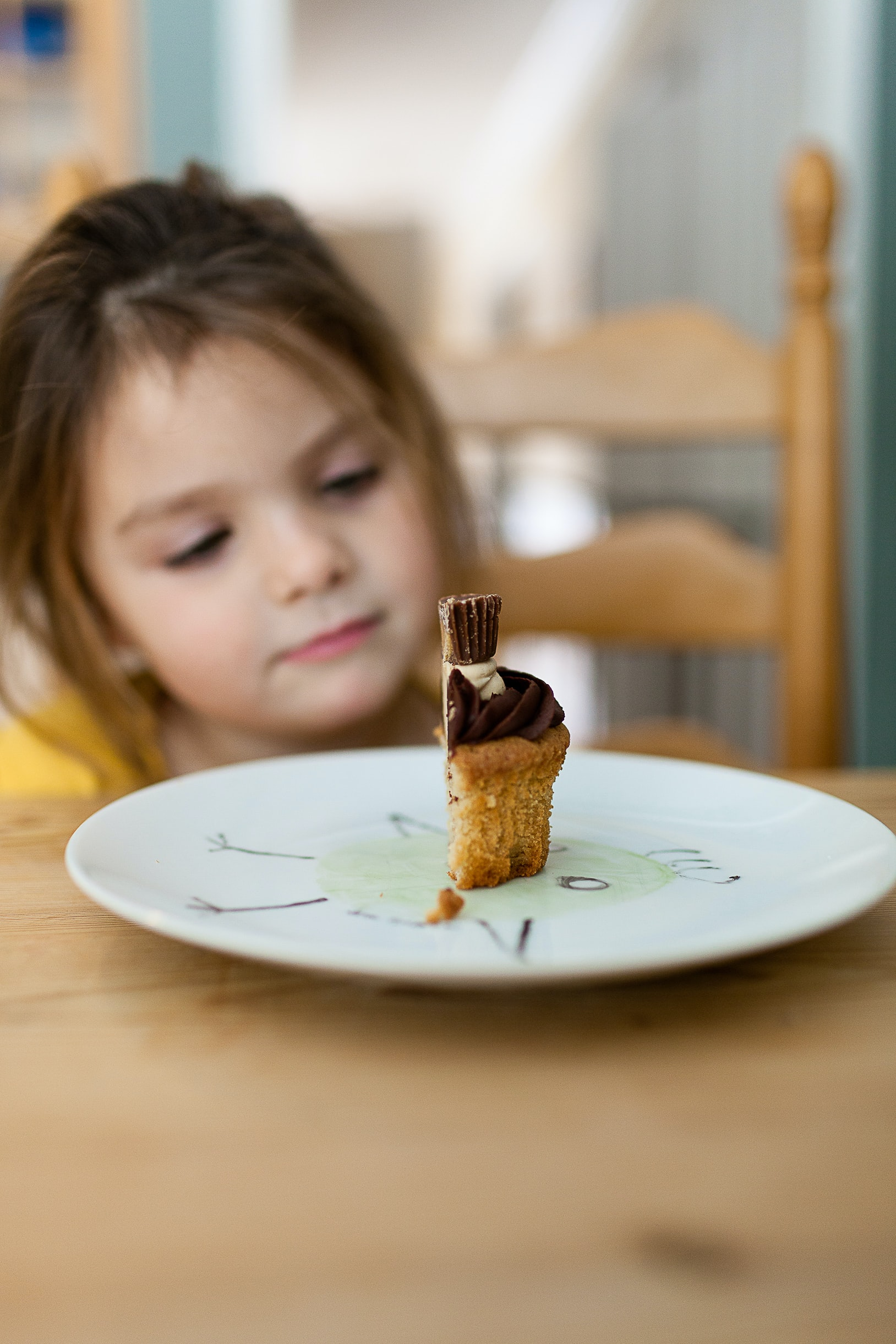 A little girl staring at half of a cupcake on a plate
