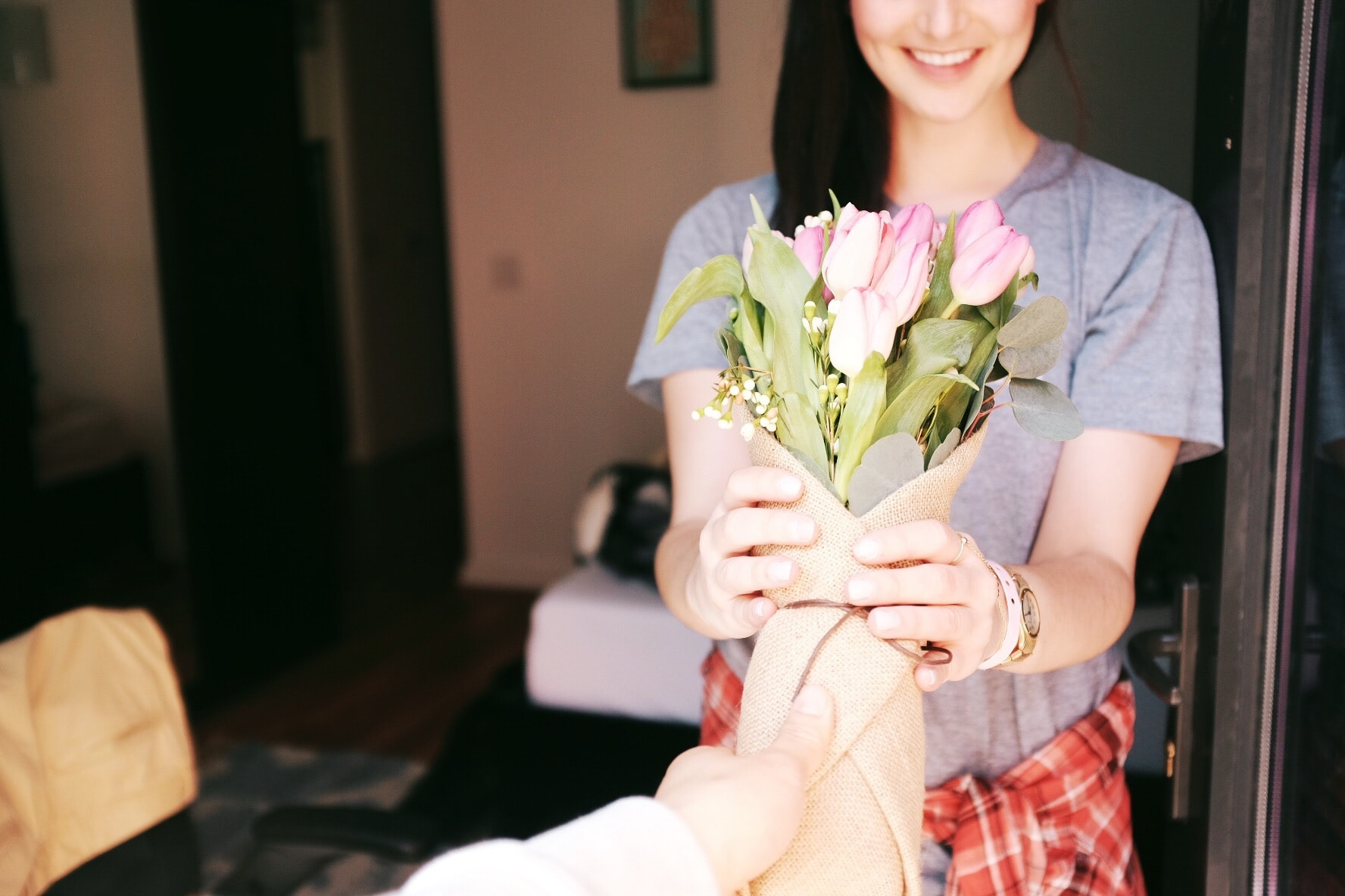Man hands a bouquet of flowers to smiling woman