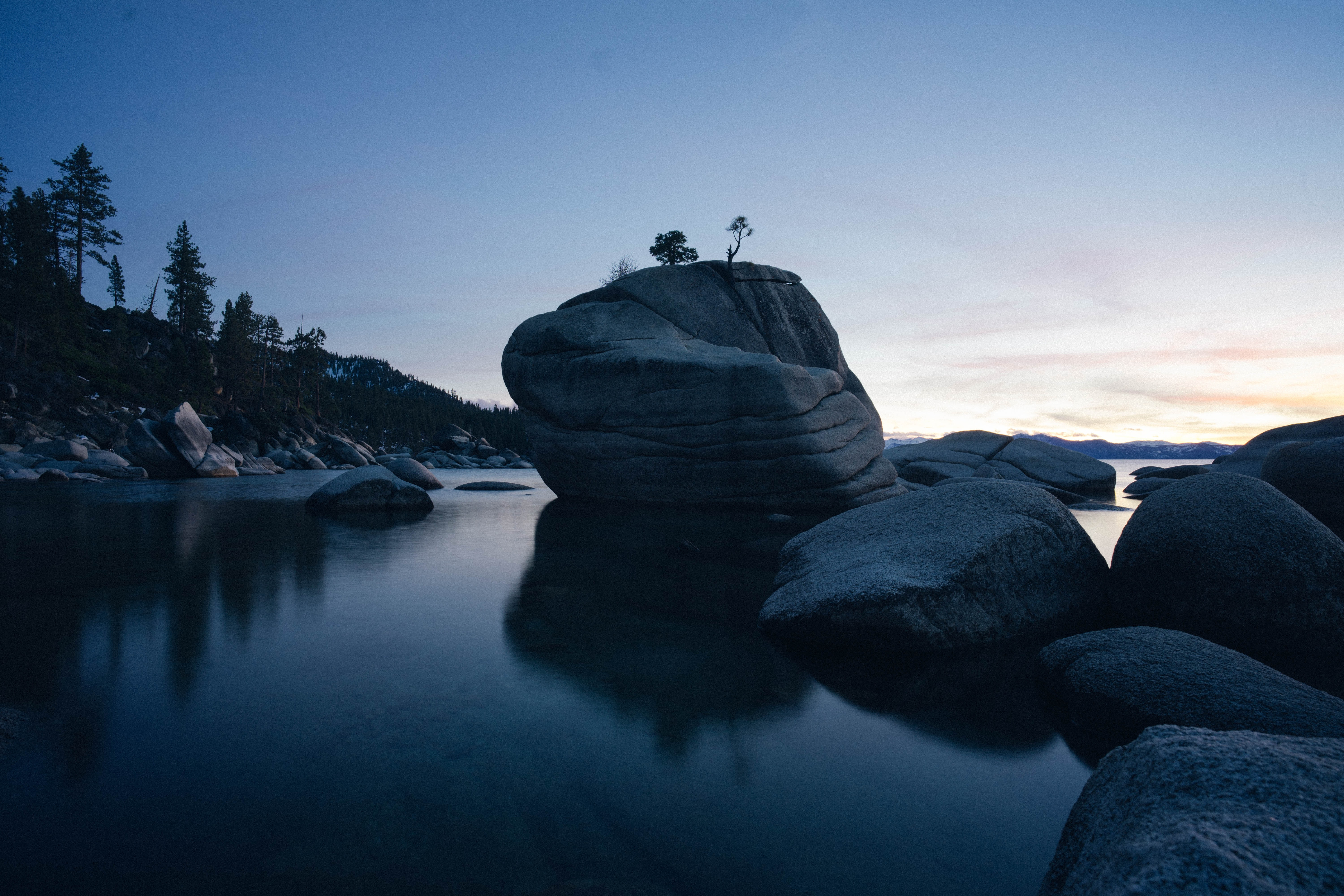rock formation on body of water at sunset