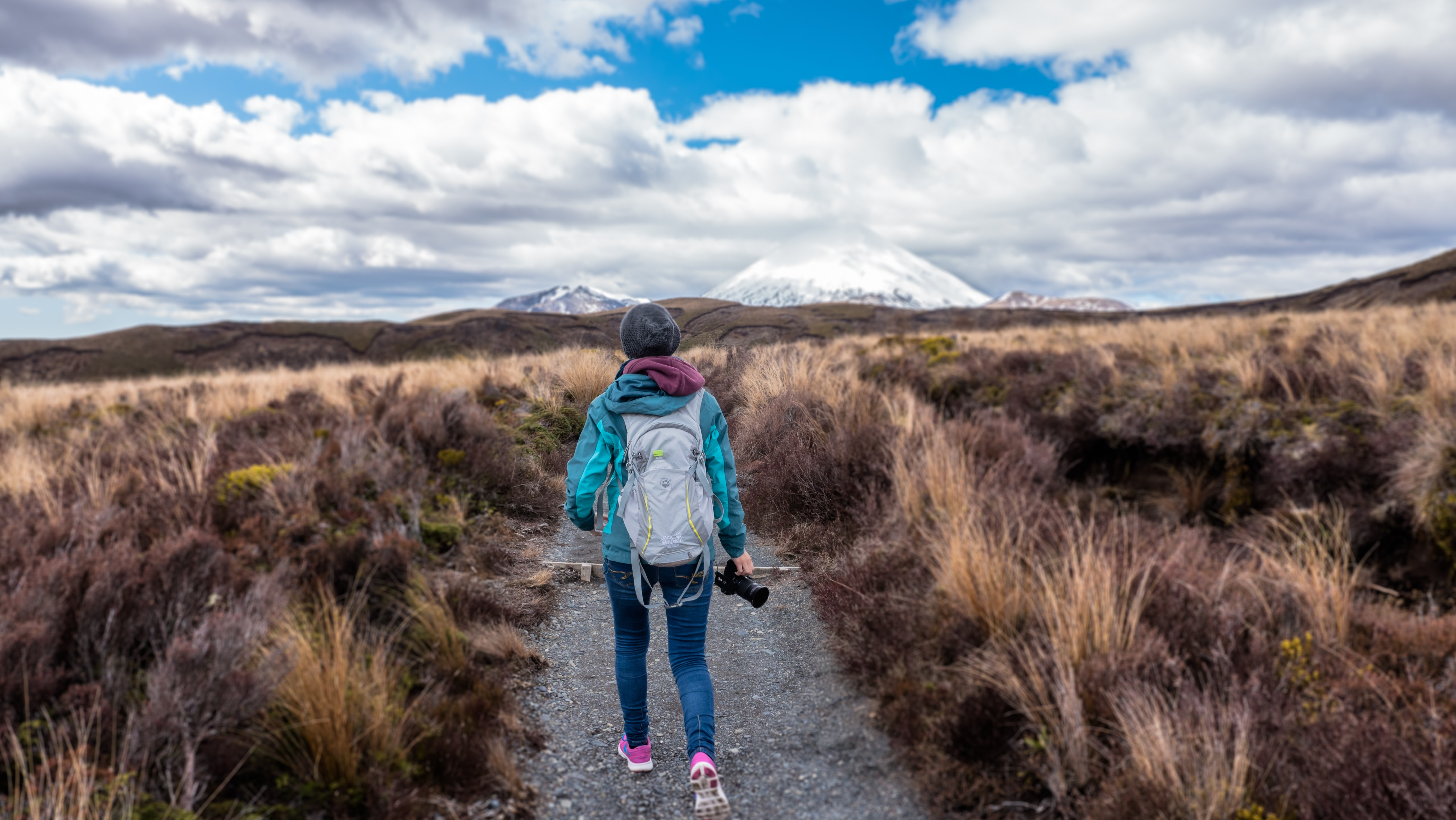 Person in jacket with backpack and camera hiking in Tongariro National Park near snowcapped mountains