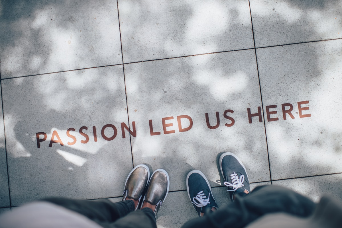 "Image of two people standing on a shadowed sidewalk with ""passion led us here"" written in red capital letters on the ground."