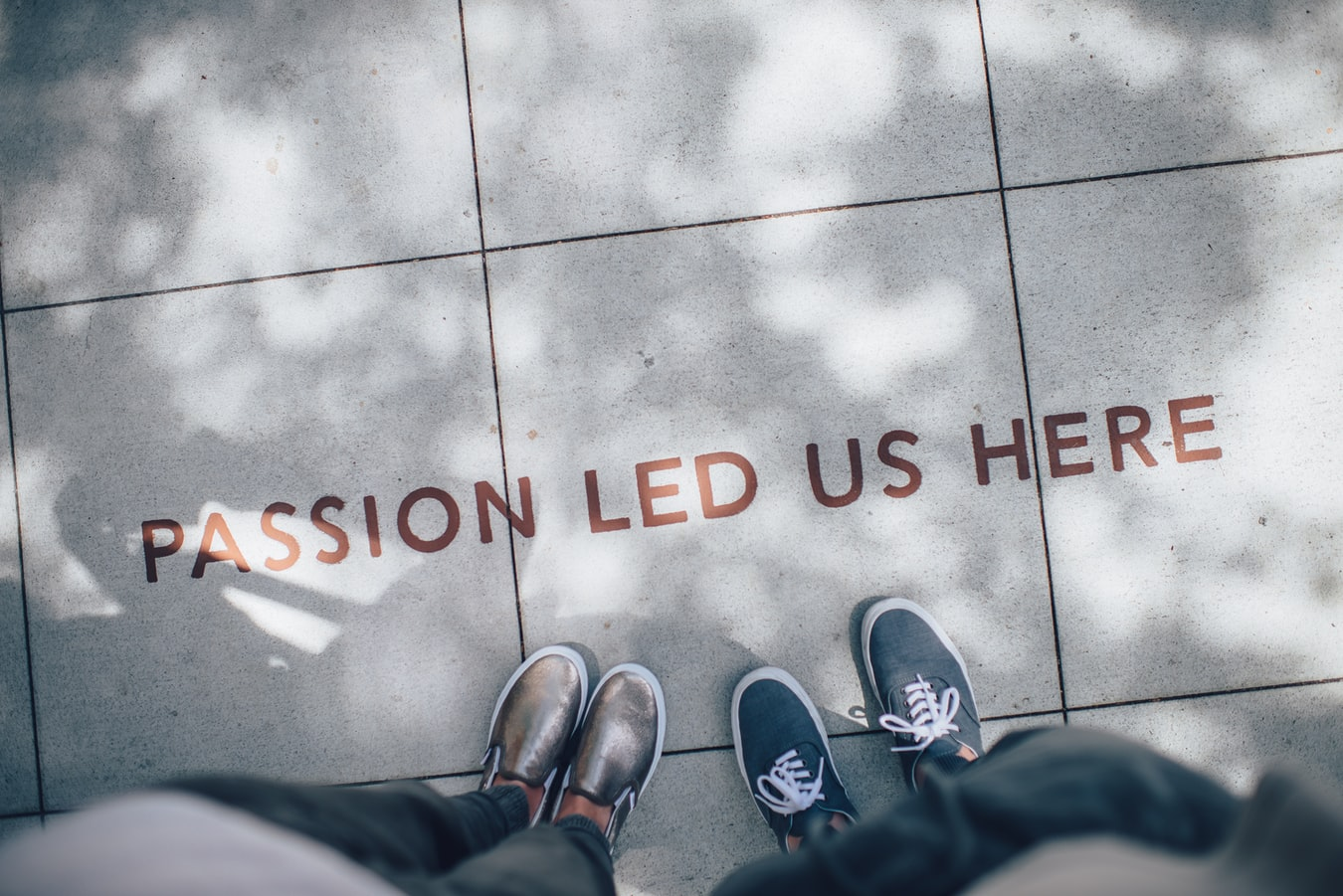 Two person standing on gray tile paving. @goian, unsplash.com