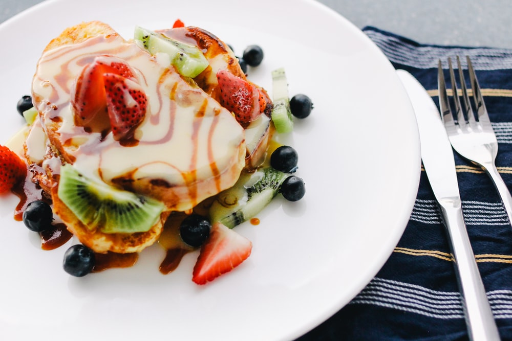 plate of pancake with strawberry and kiwi toppings