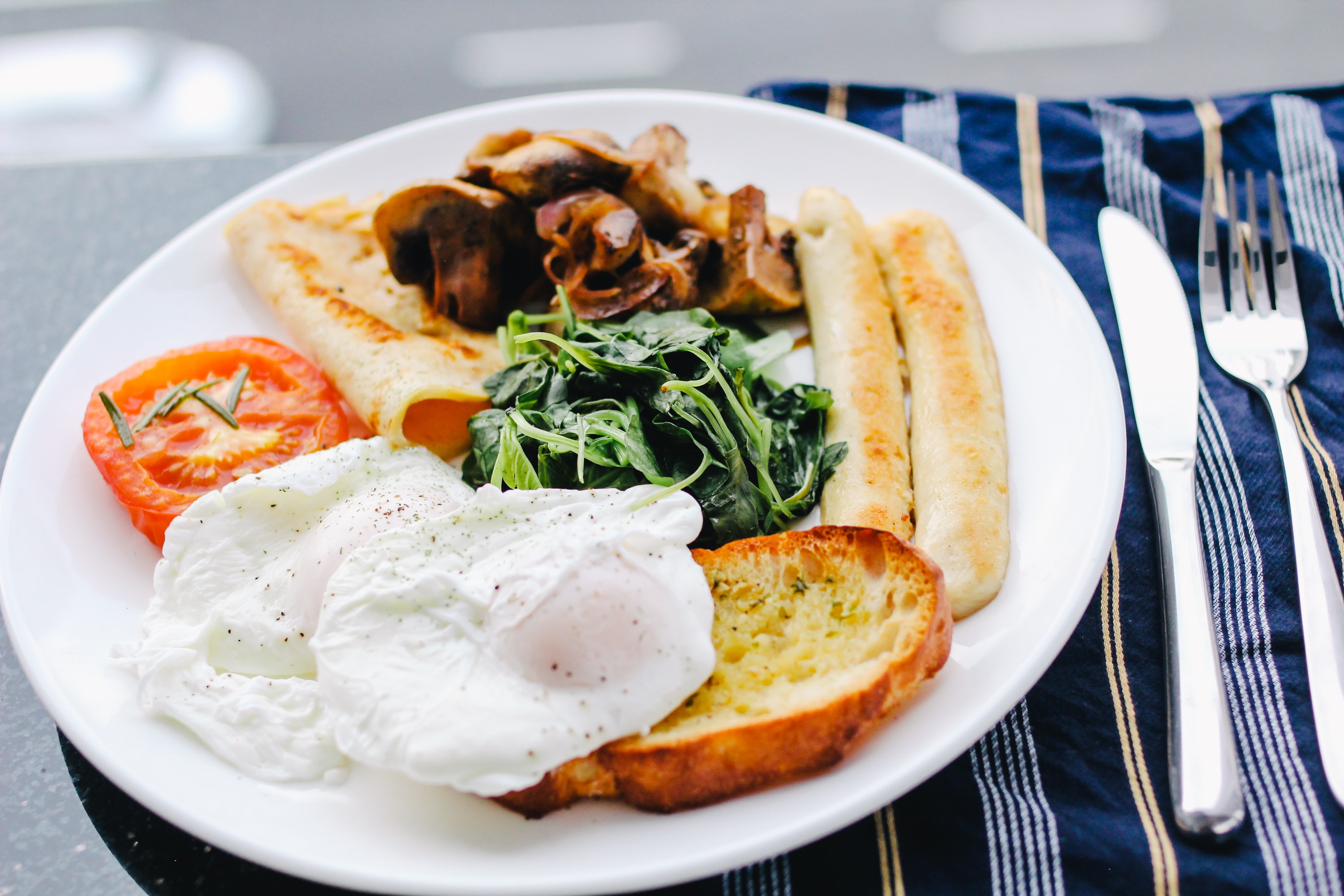Hearty breakfast with eggs, toast, tomato, and vegetables