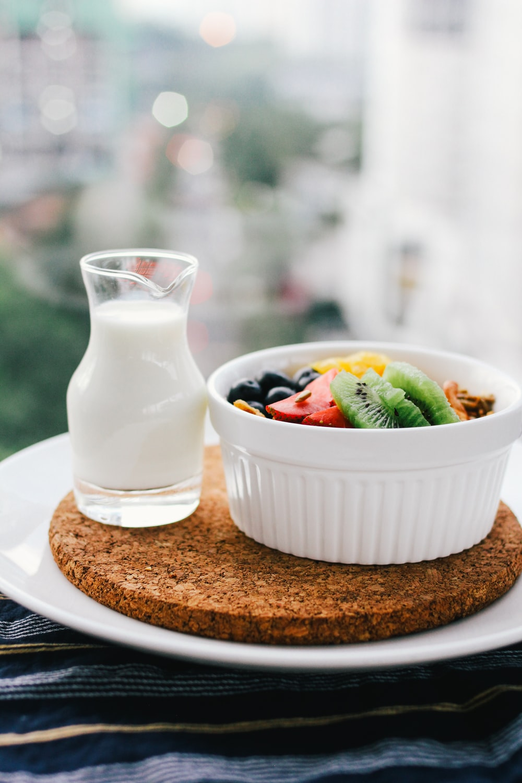 fruit salad inside bowl beside glass of milk on brown board