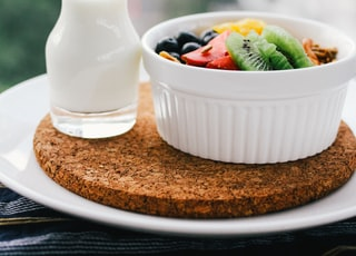fruit salad inside bowl beside glass of milk on brown board
