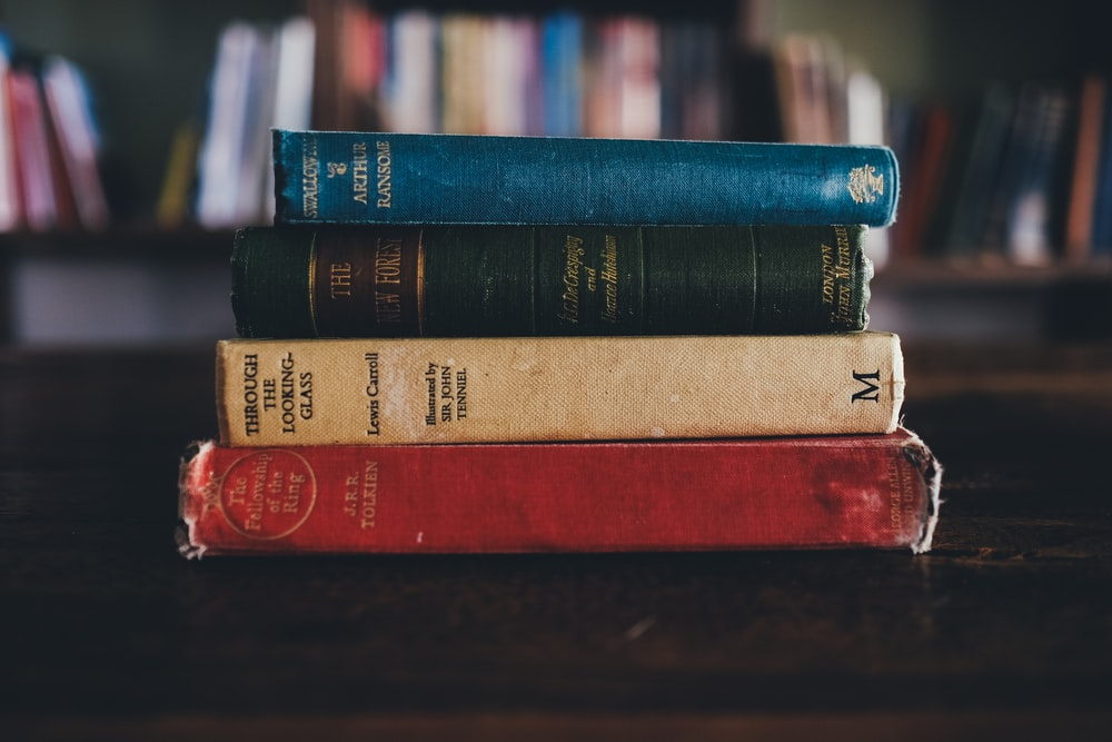 four assorted reading books on brown surface