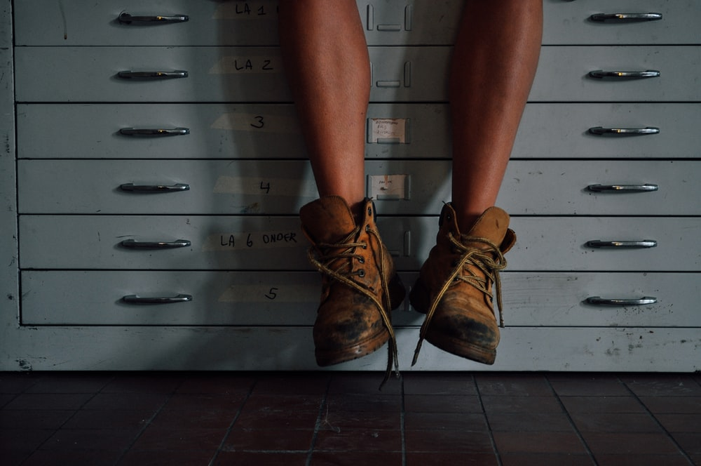 person wearing brown work boots on cabinet