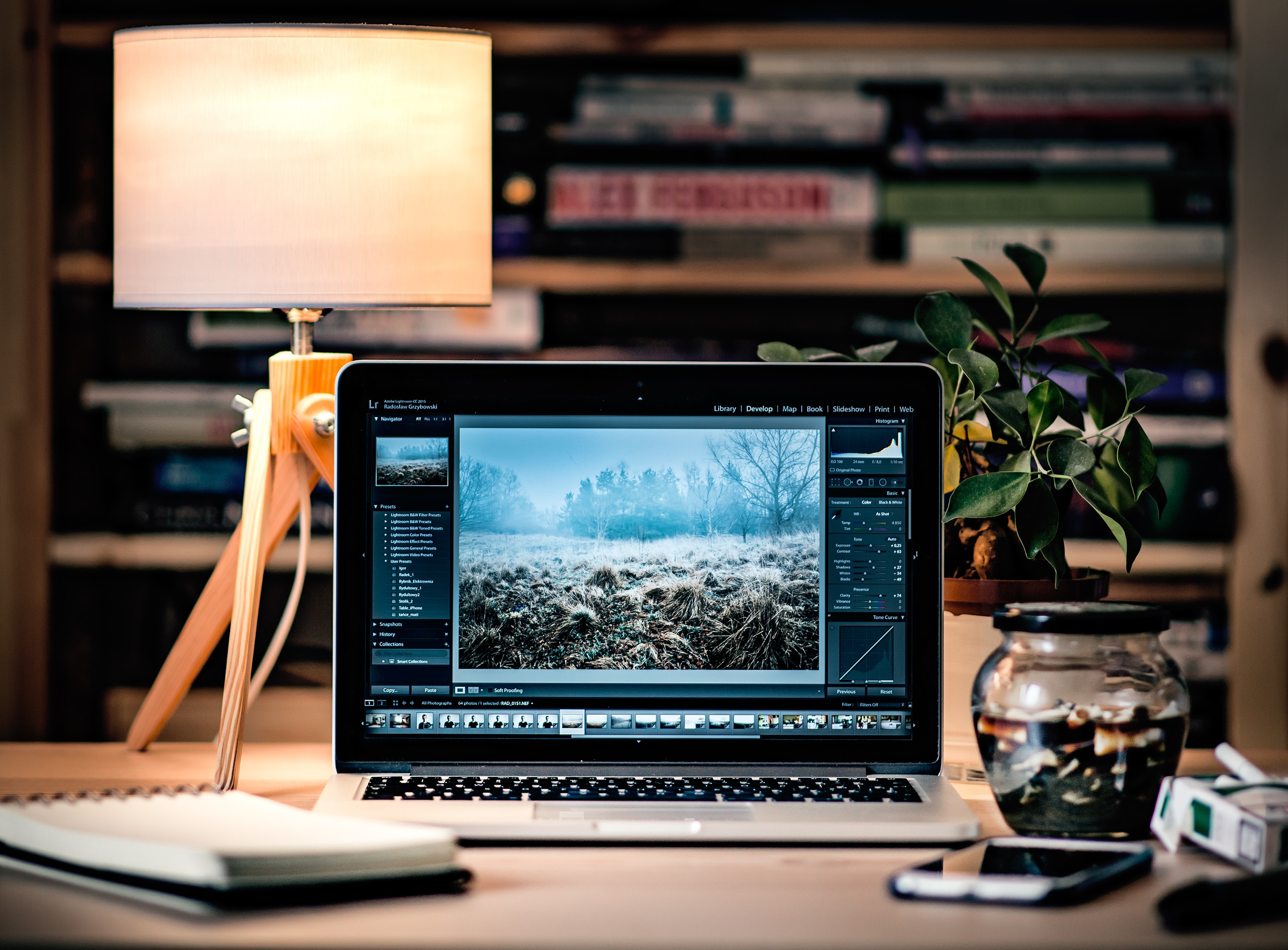 A MacBook with photo editing software on a busy desk
