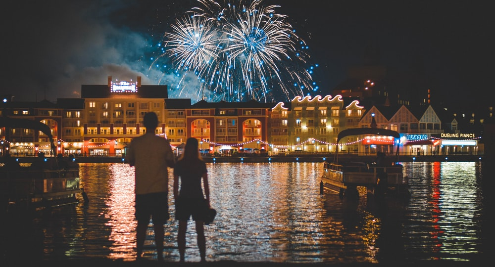 two people standing beside body of water watching fireworks