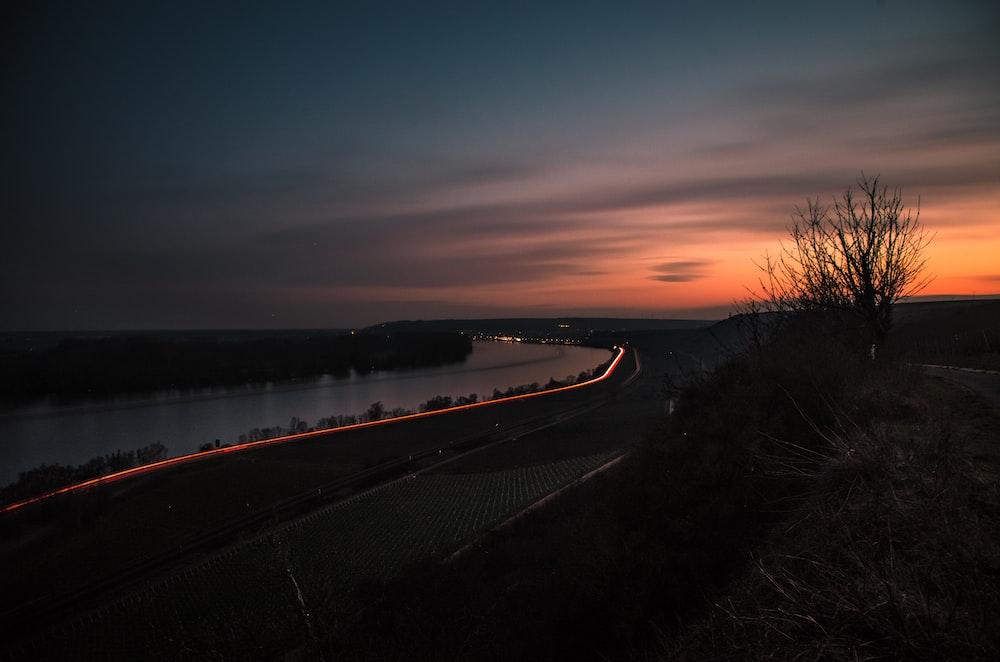 black asphalt road near body of water during sunset