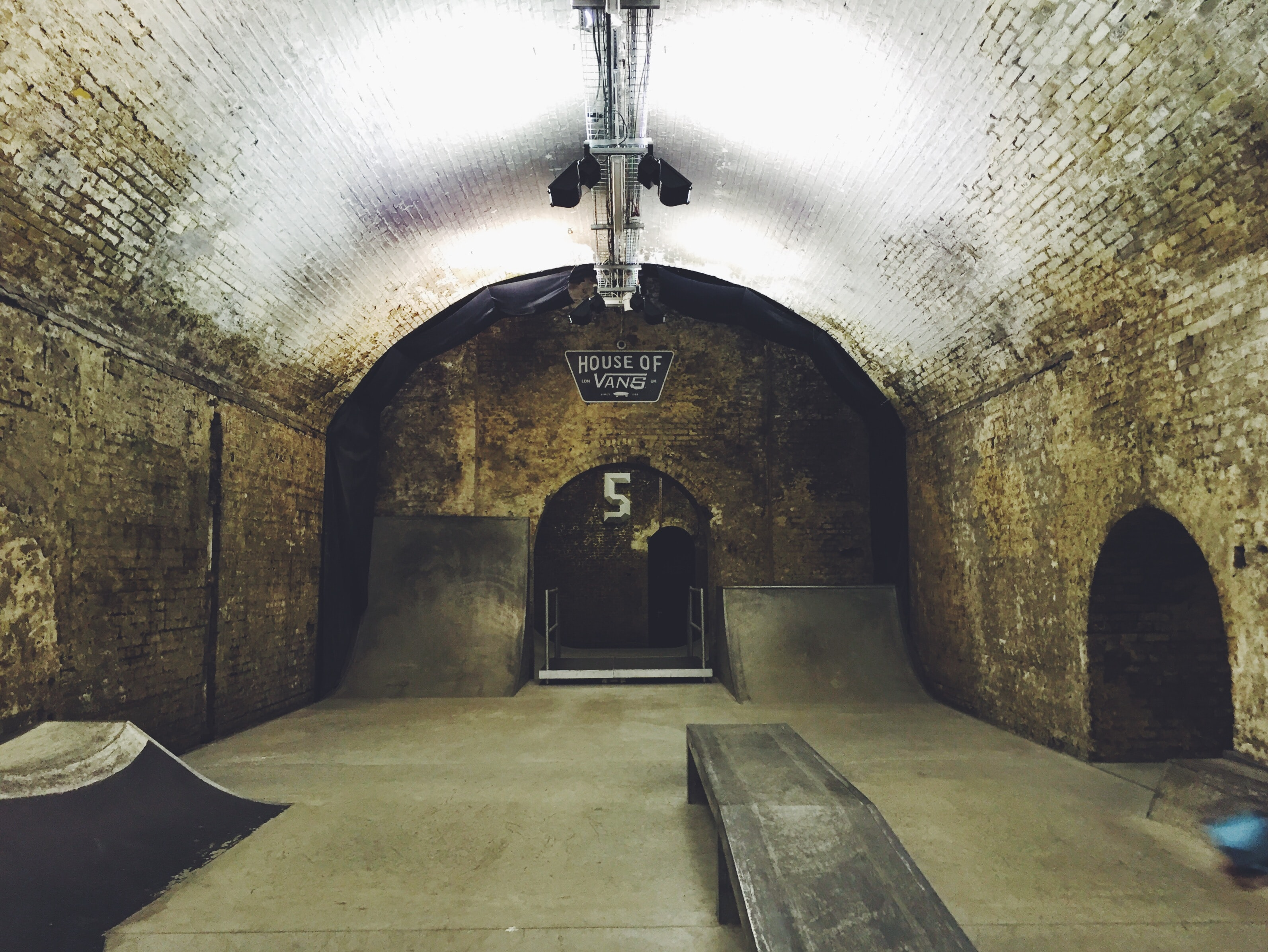 Old tunnel with bricks walls and domed ceiling converted into a skateboarding room complete with ramps and lights