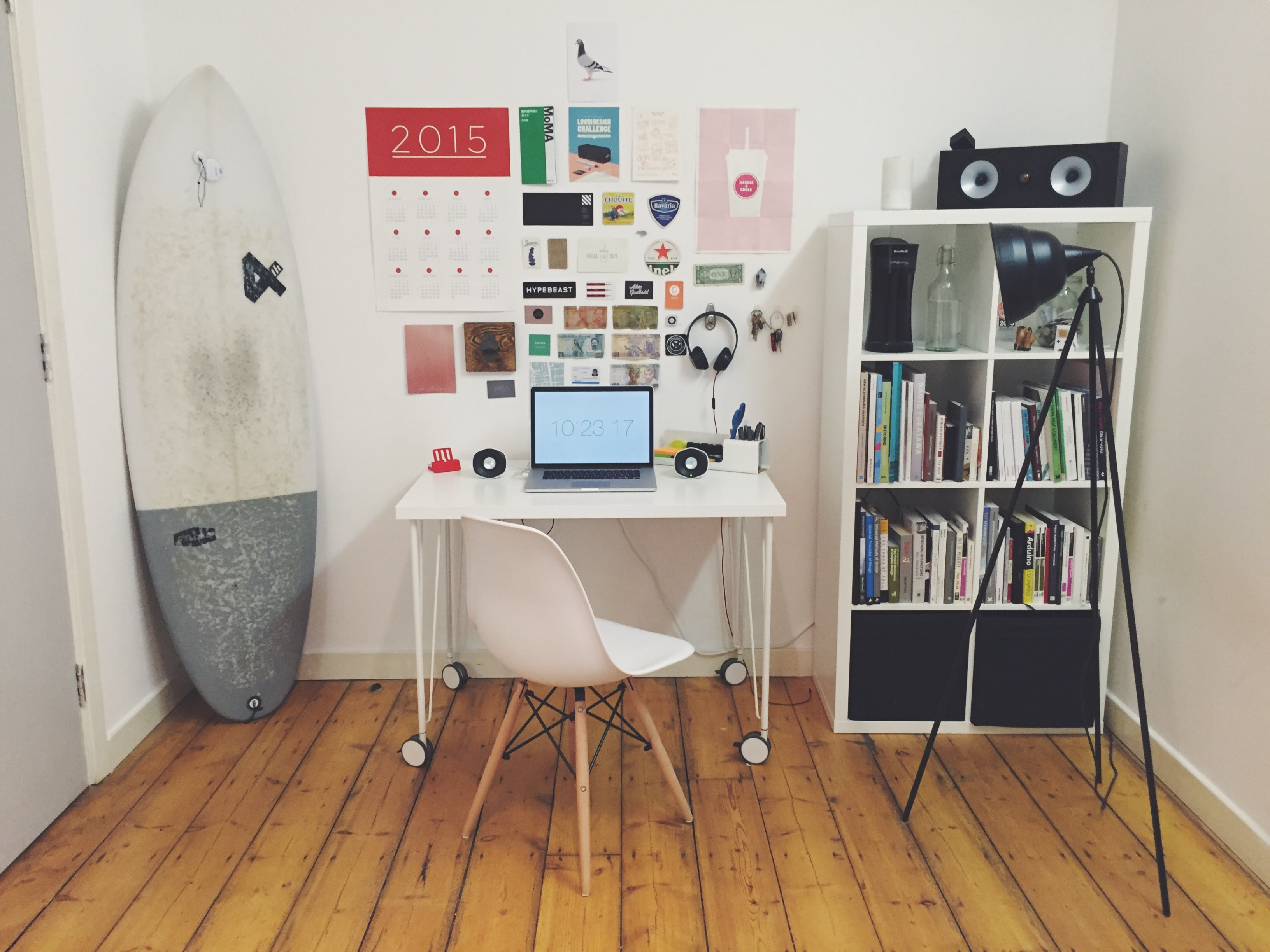 A small home office with a surfing board in the corner next to a desk on wheels