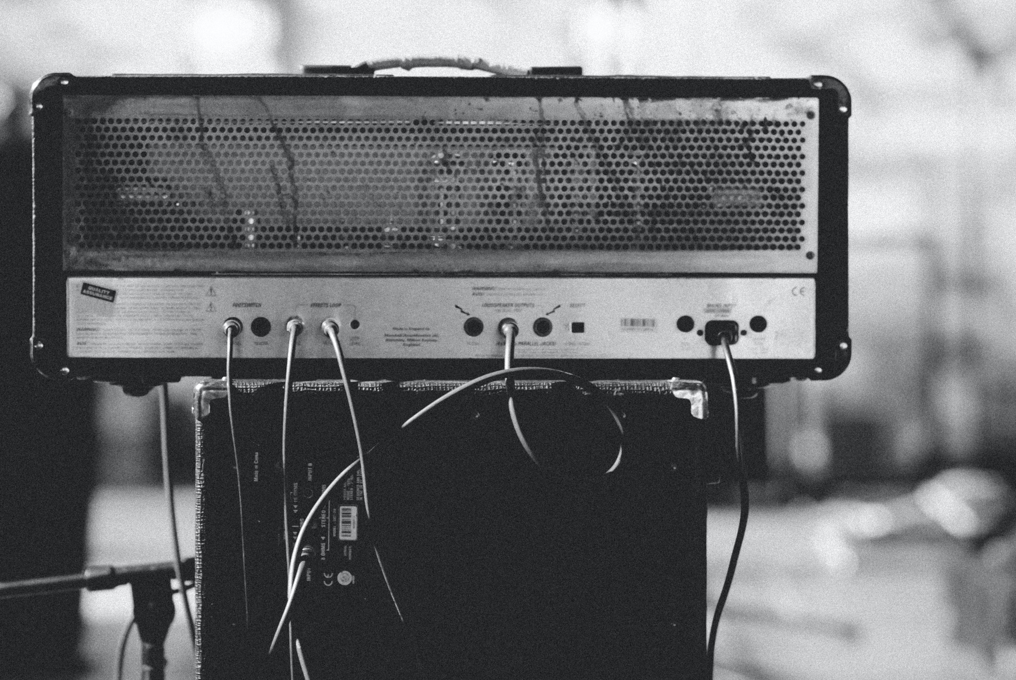 Black and white close up of shot of amplifier with cables and cords