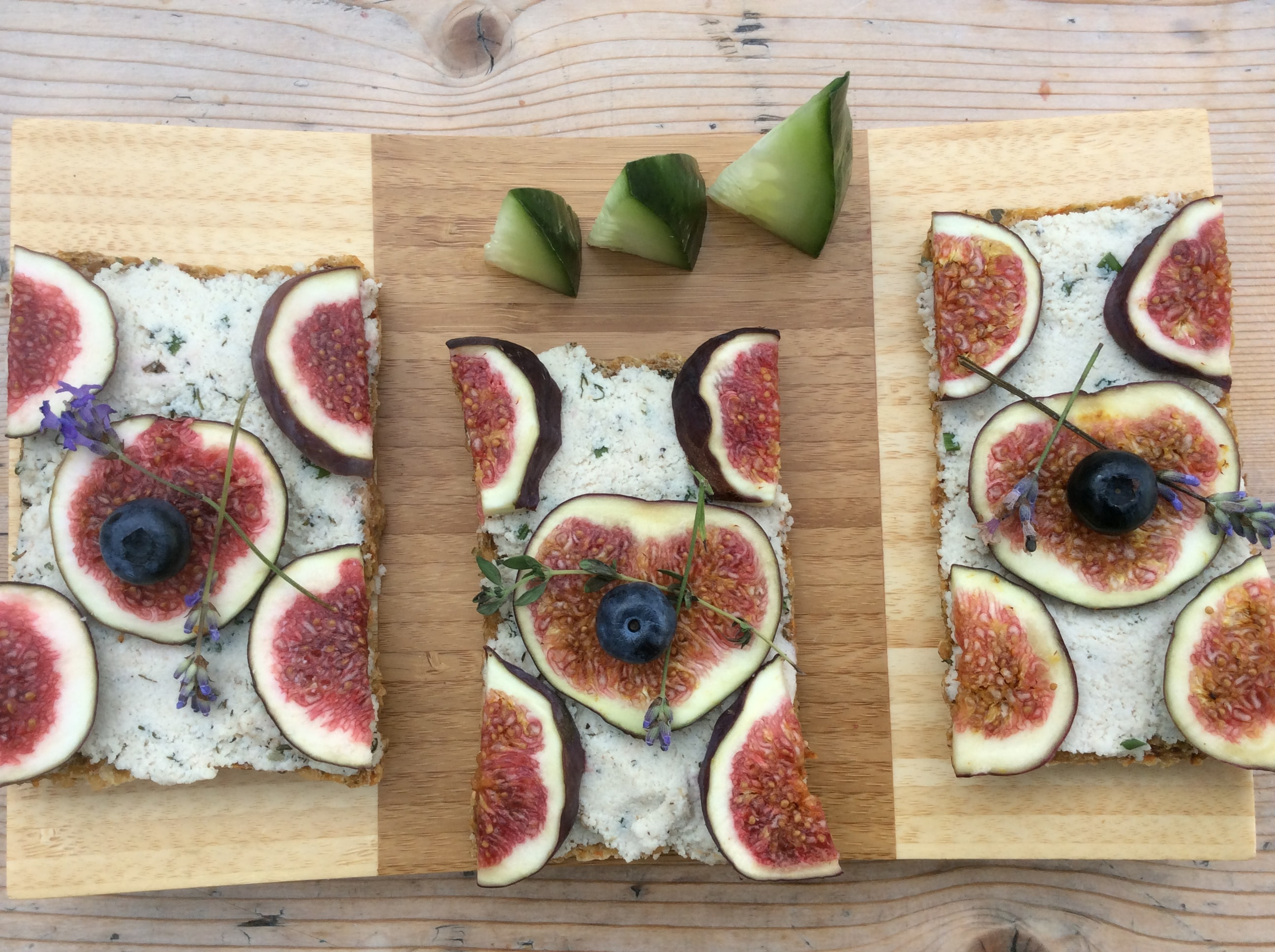 Slices of bread with fresh figs and cucumber dill spread on a cutting board