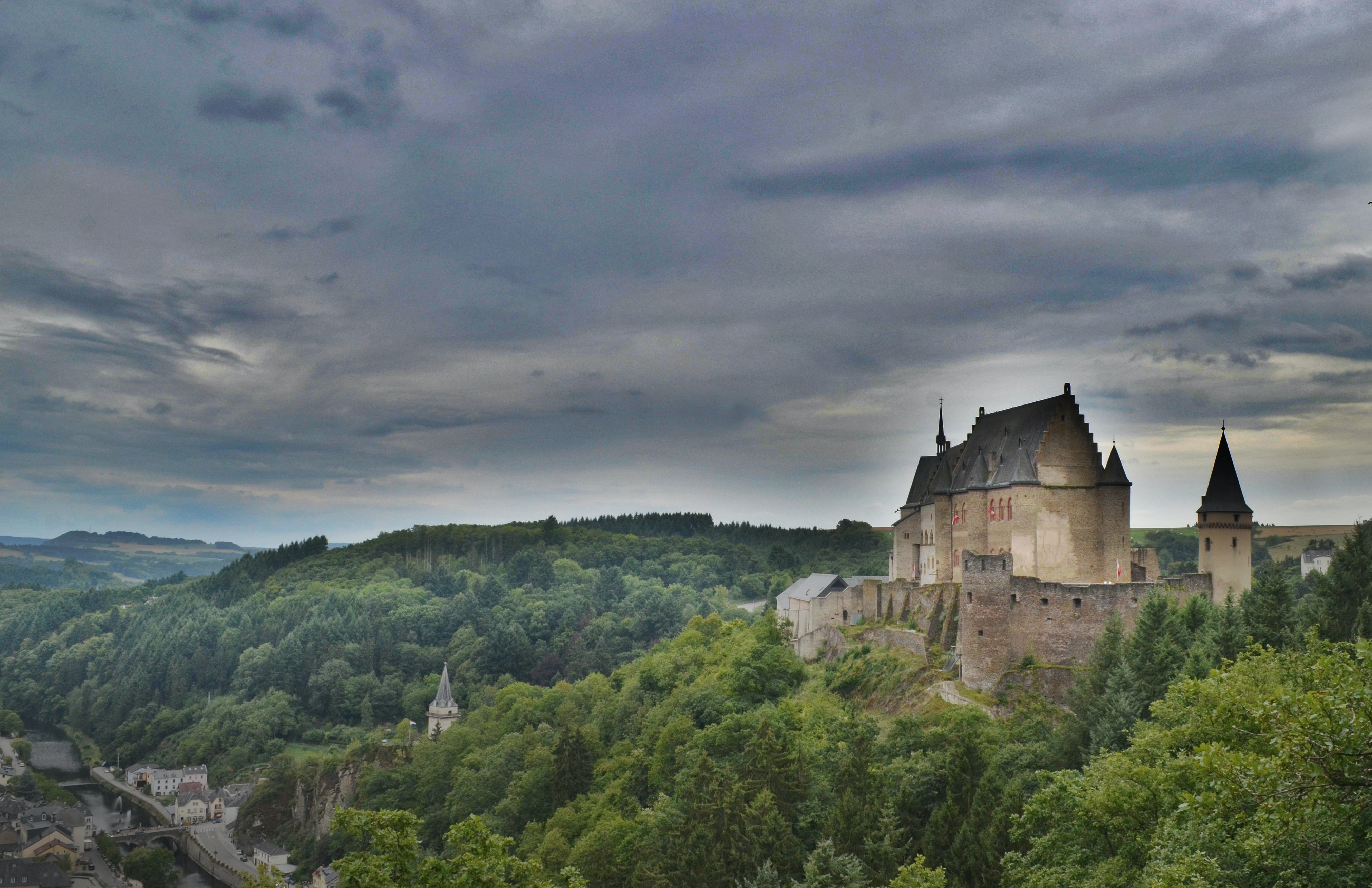 A medieval castle on a hill near a town in Luxembourg