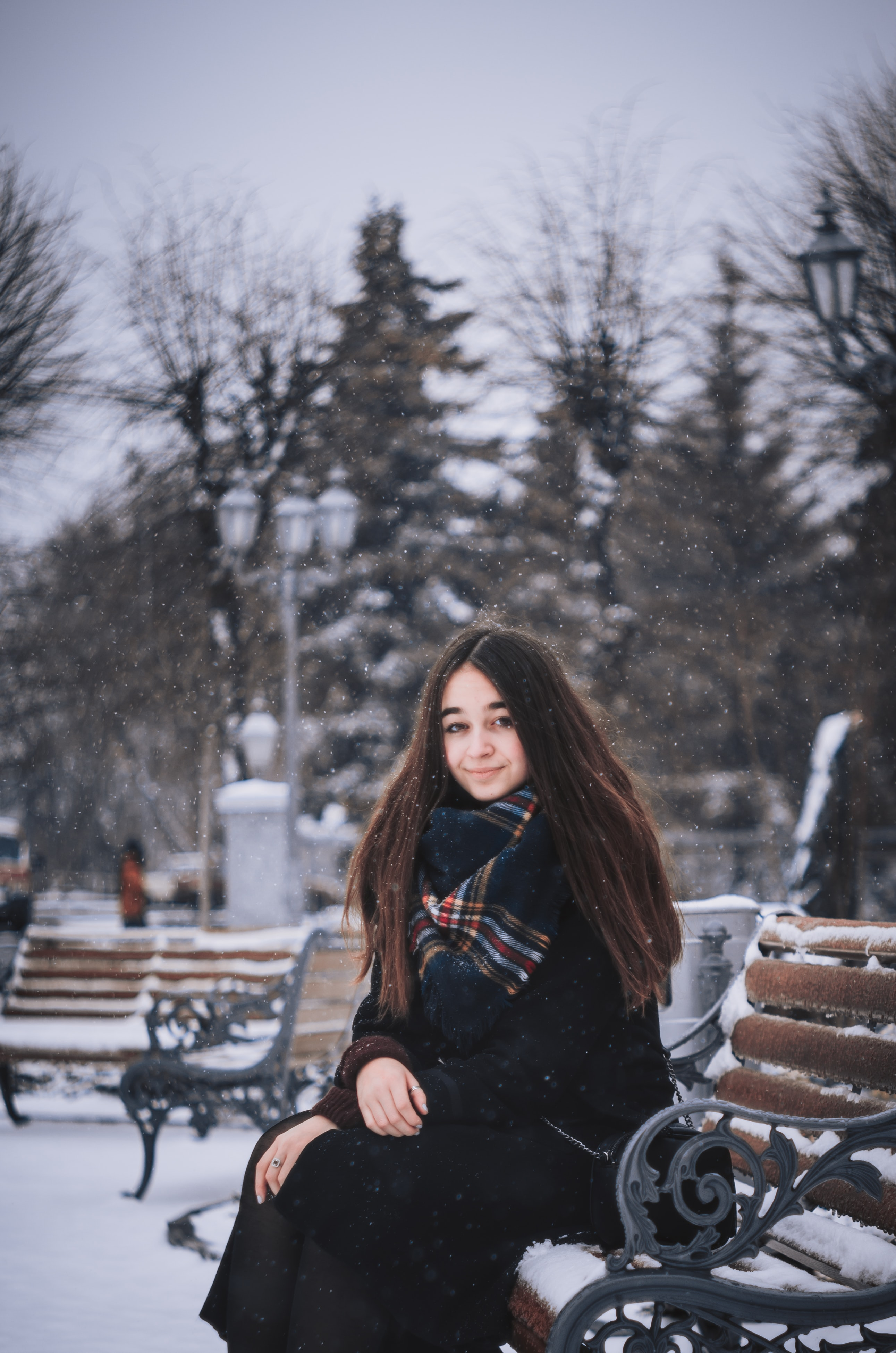 A smiling woman in a scarf sits on a park bench in the snow