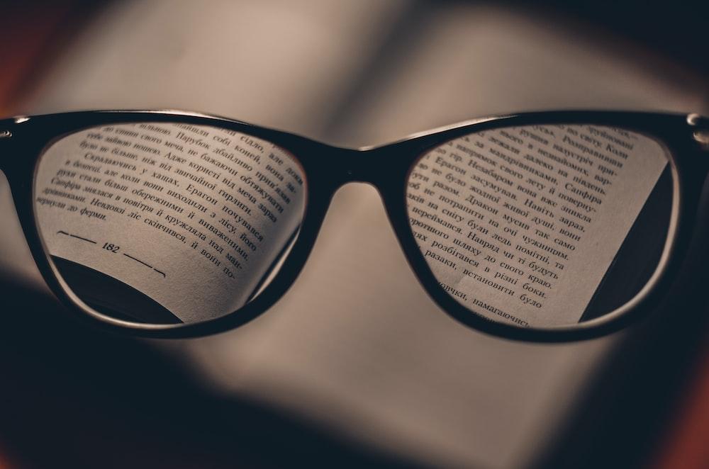 An open book in Ukrainian seen through a pair of glasses