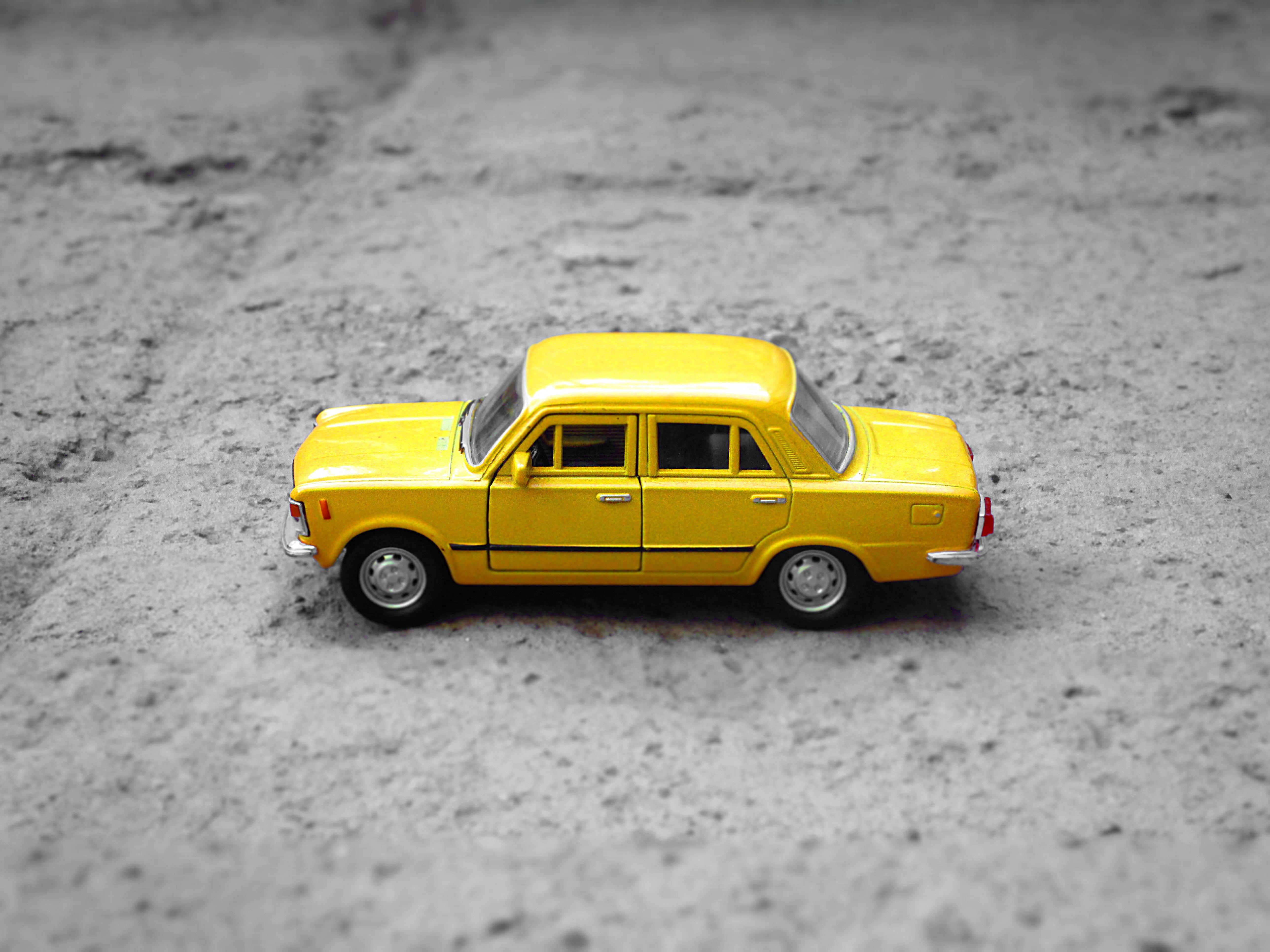 Miniature yellow toy taxi cab on sidewalk