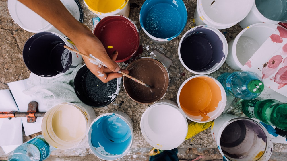 Artist dips paintbrush in bucket of paint among other pots of different colored paint