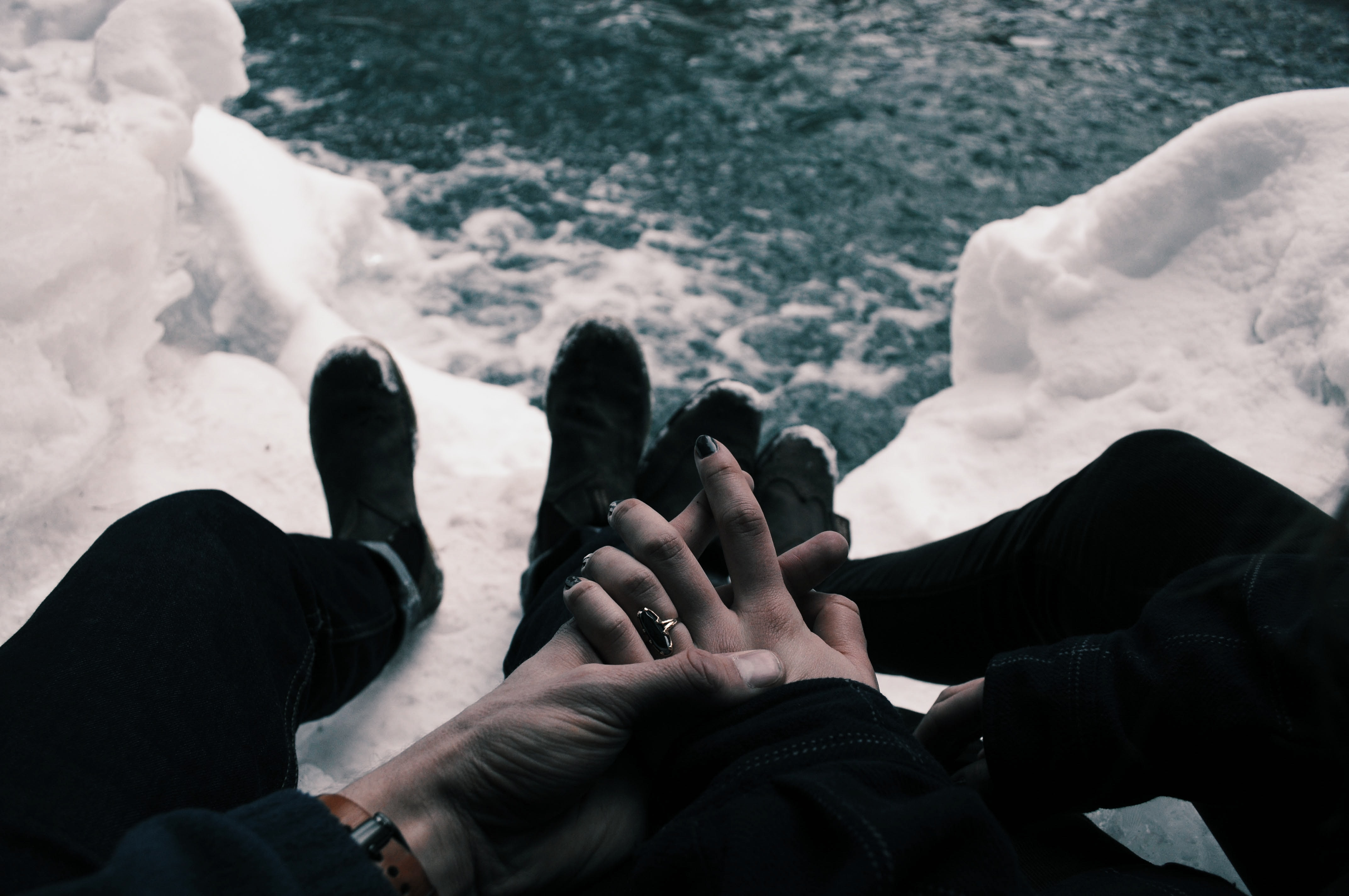 Couple with hands clasped while sitting on icy mountaintop overlooking water