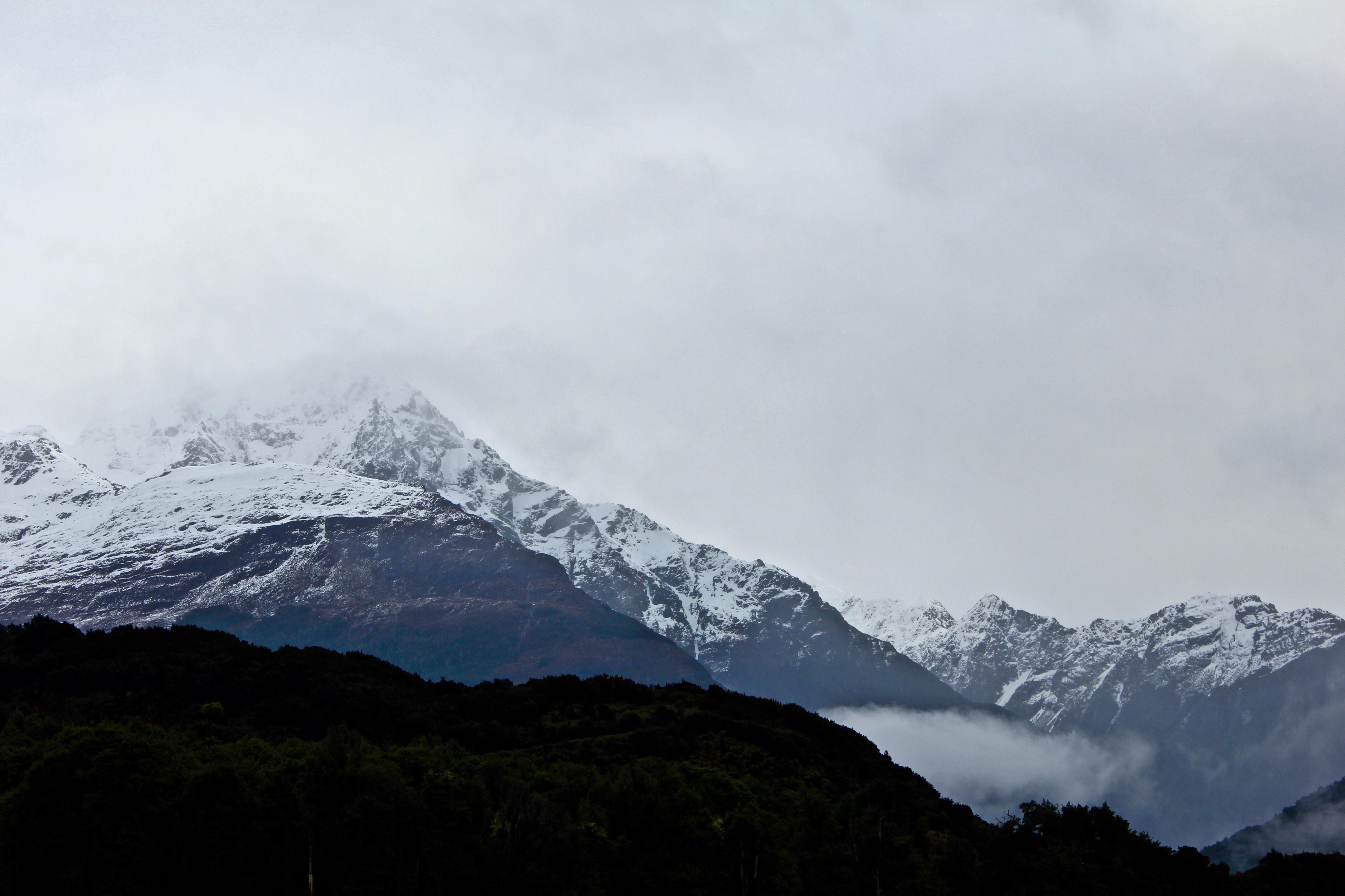 Snow-capped mountains fade into a foggy sky
