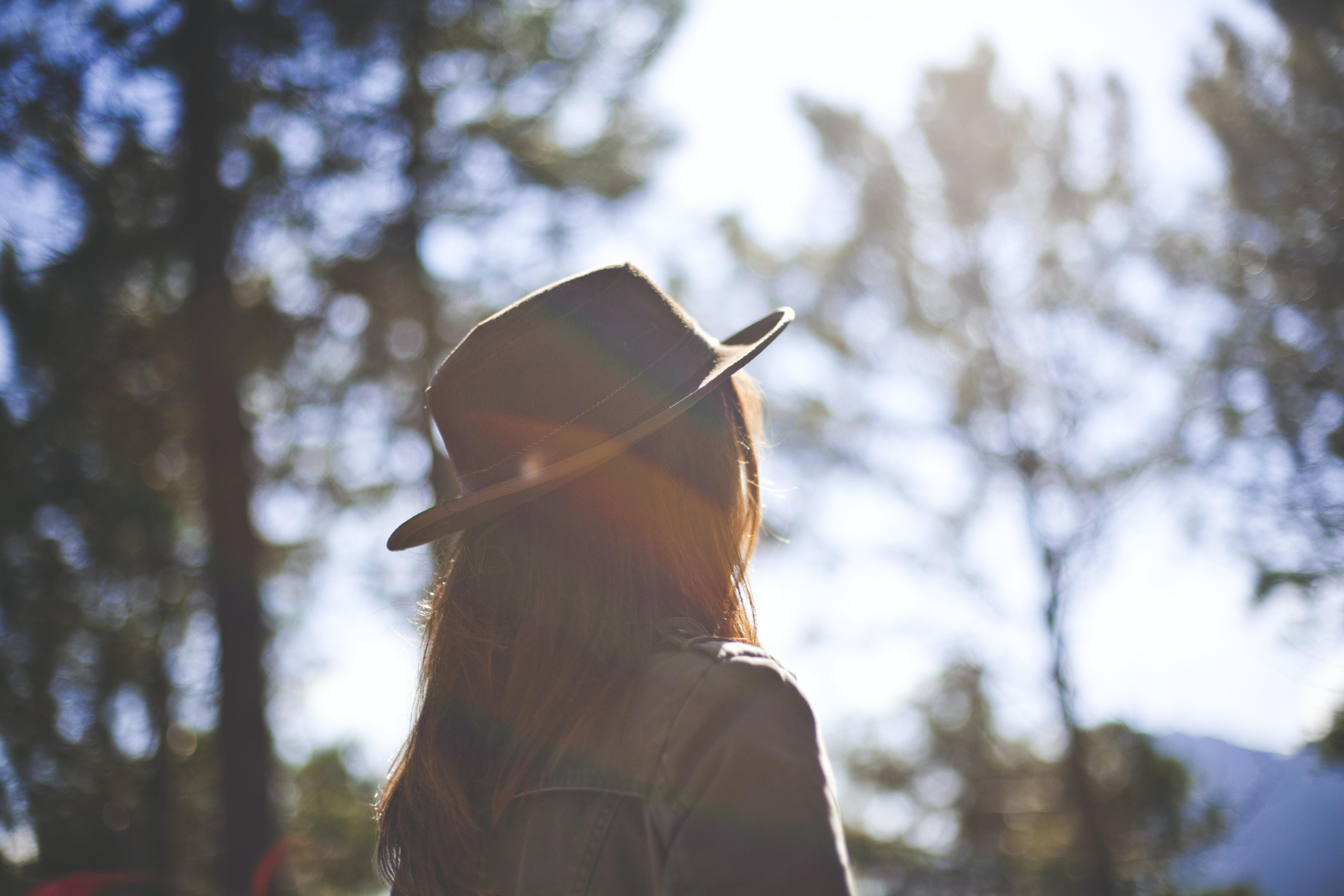 woman wearing hat standing facing tree