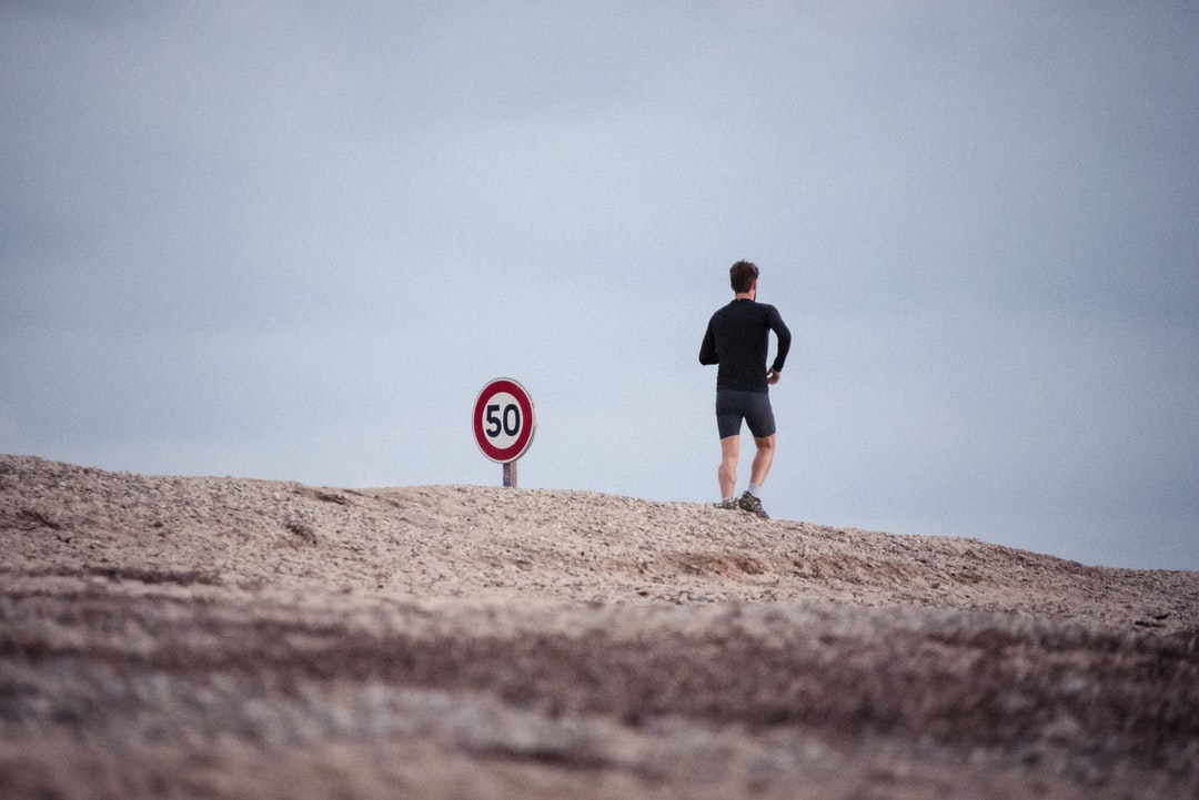 Guy jogging by sign