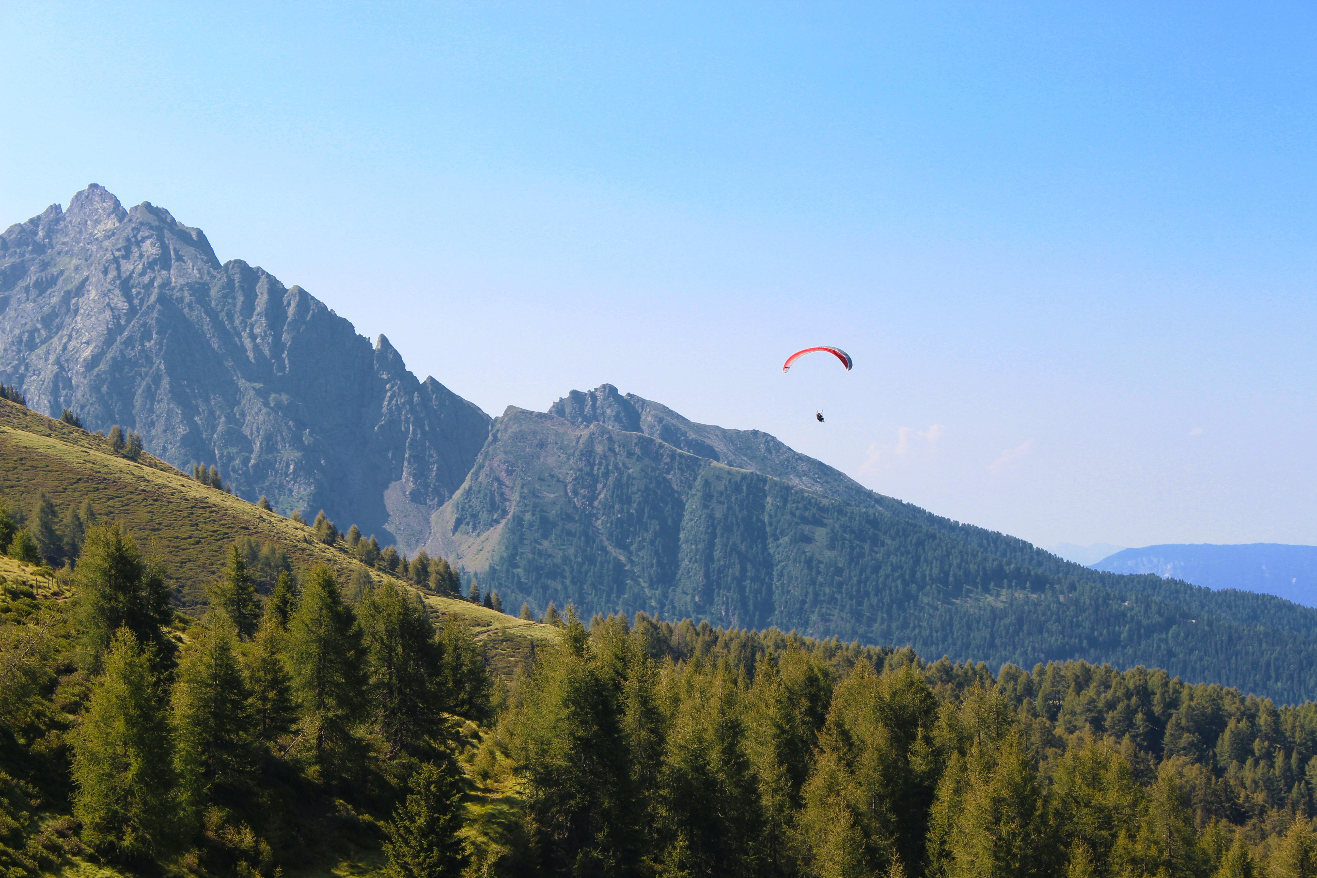 A paraglider in the air over mountains in Italy